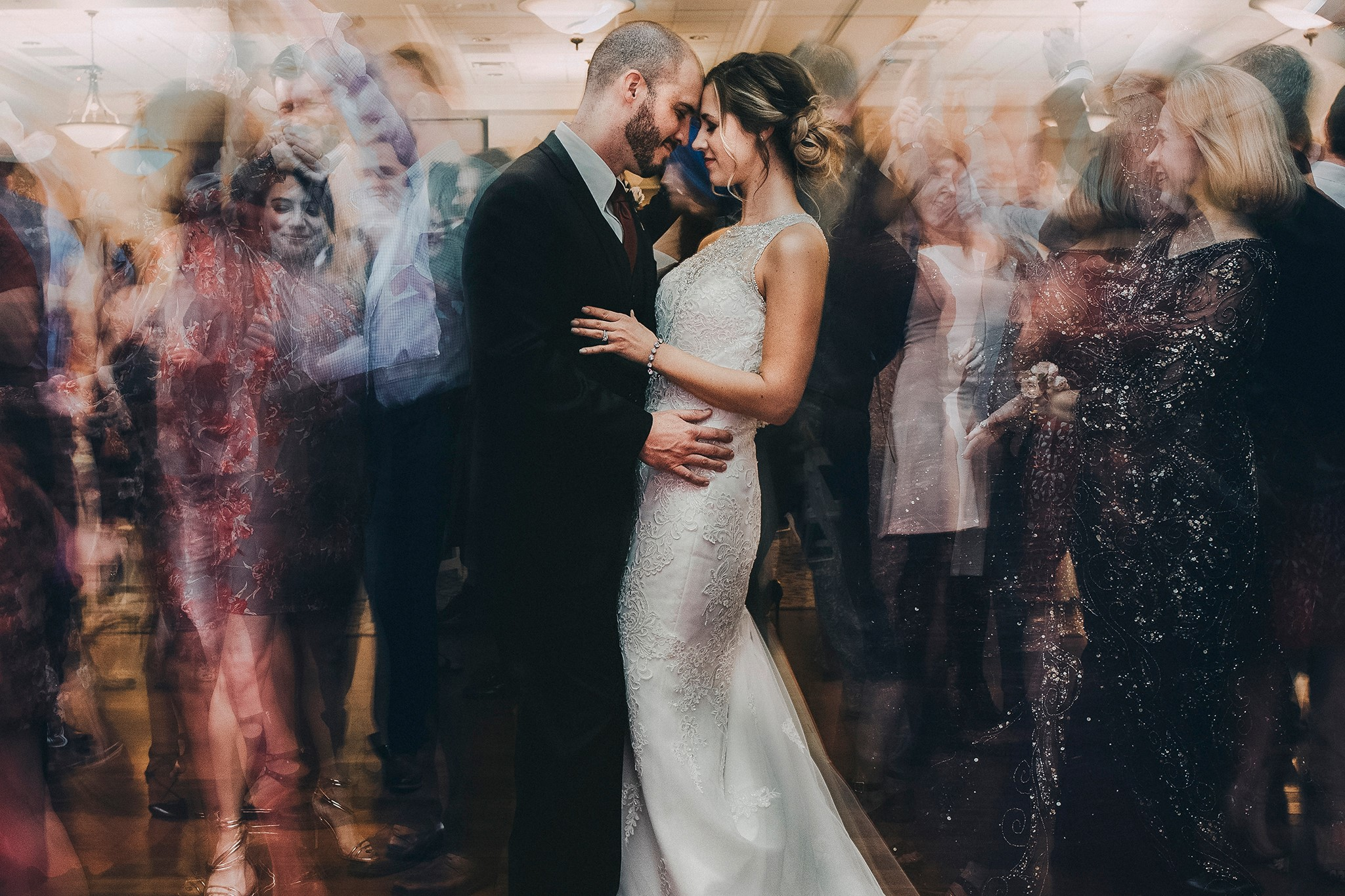 Bride and groom in the middle of the dance floor as their party is slowed down behind them. A perfect and unique wedding photo