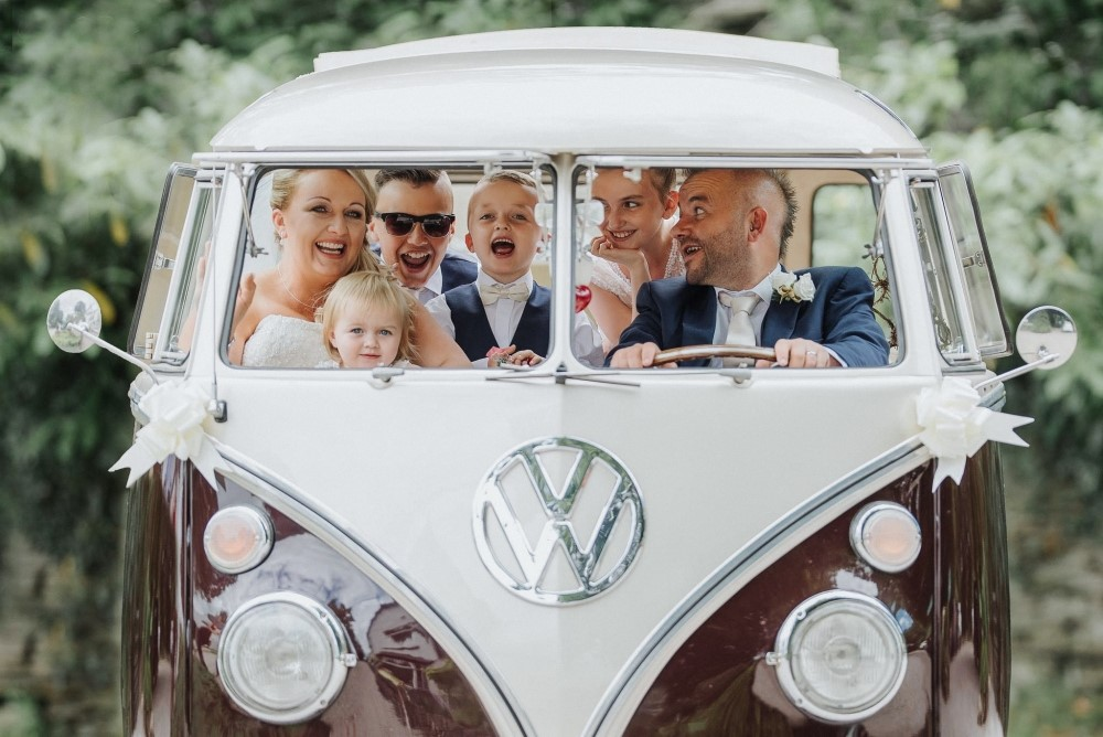 A family wedding photo in a vintage Volkswagen camper van| The couple are full of happiness and in love