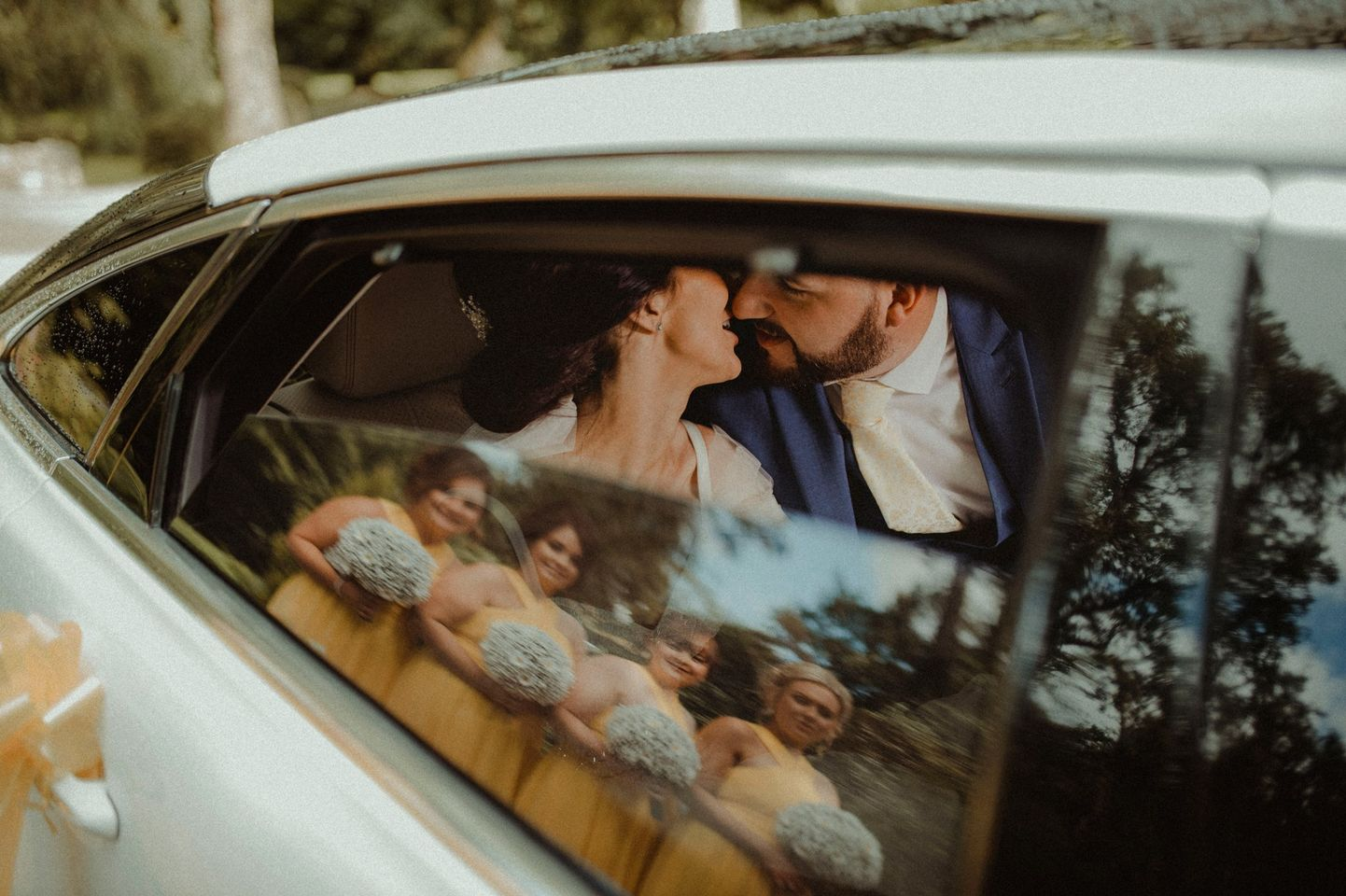 Bride and groom in the wedding car as bridesmaids are in the reflection of the car window| Romantic Autumn Wedding