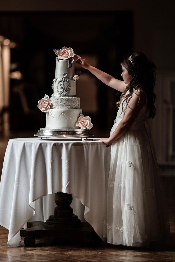 Daughter touching the wedding cake
