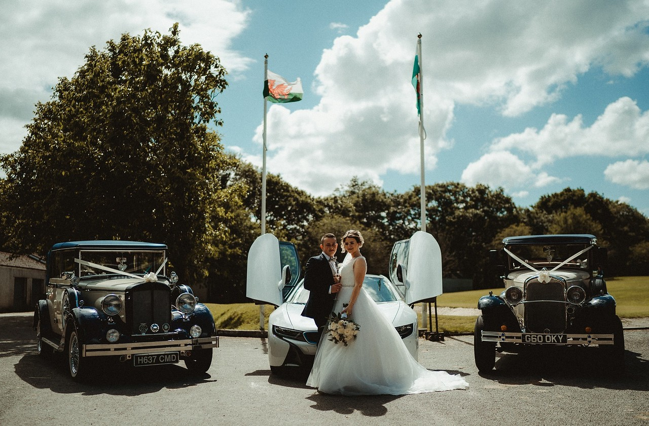 Bride and groom with wedding cars at the venue
