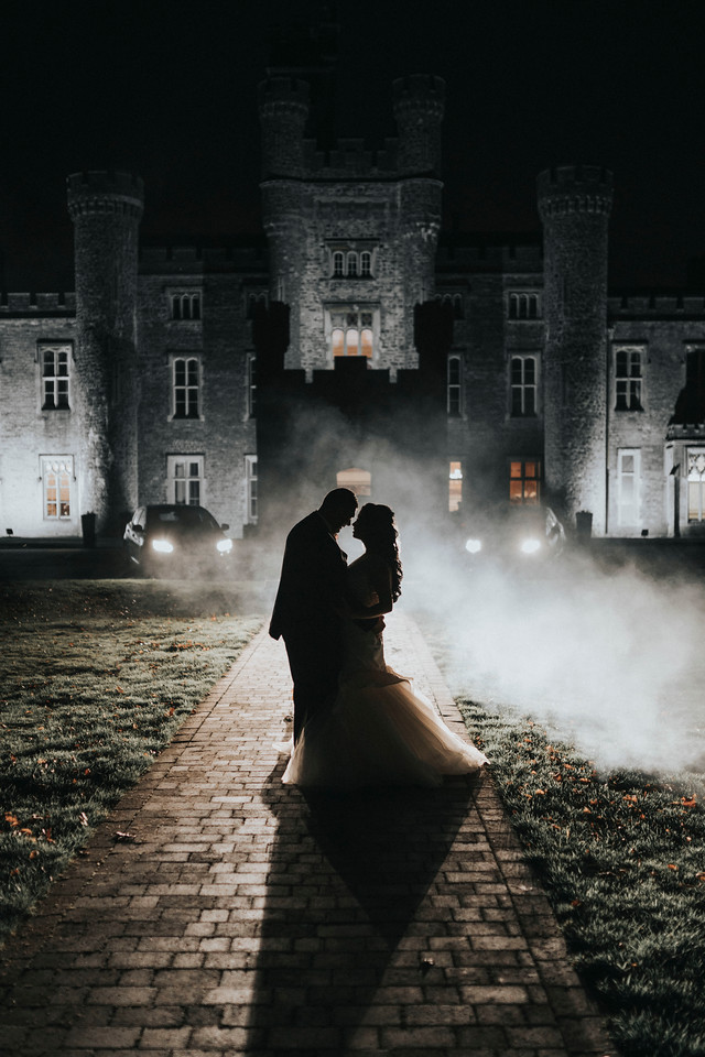 couple share their love into the night, lights reflect onto the couple