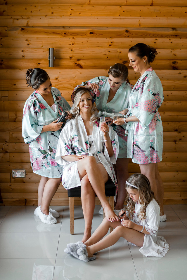 Bridesmaids get the bride ready for her big day. The bride is full of smiles