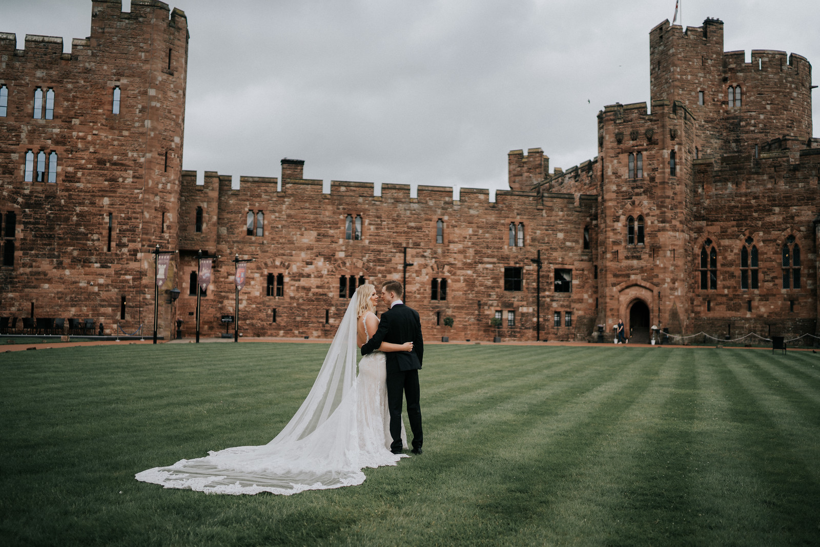 bride and groom stands in front of their castle venue