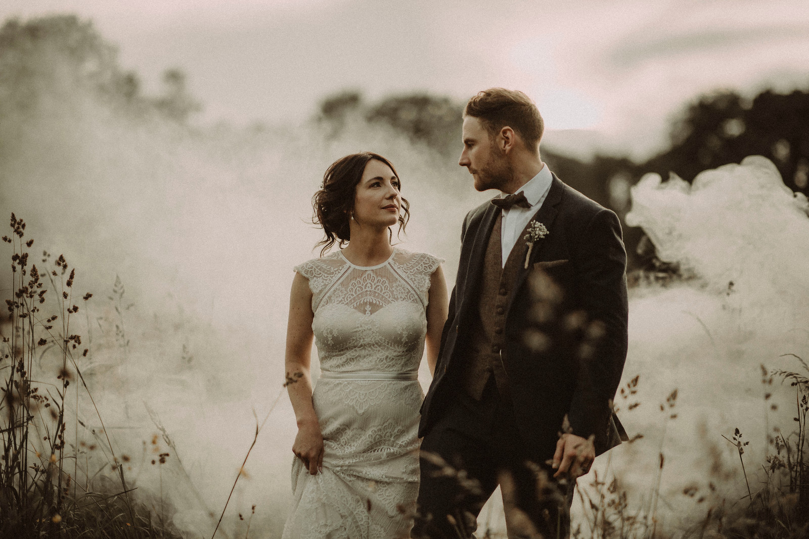 Bride and groom walk through the countryside whilst looking at each other. Smoke is in the background