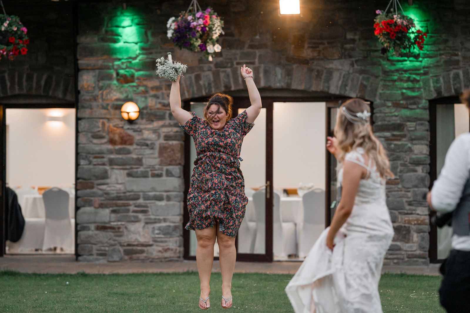 The guest jumps for joy as she caught the flowers of the bride