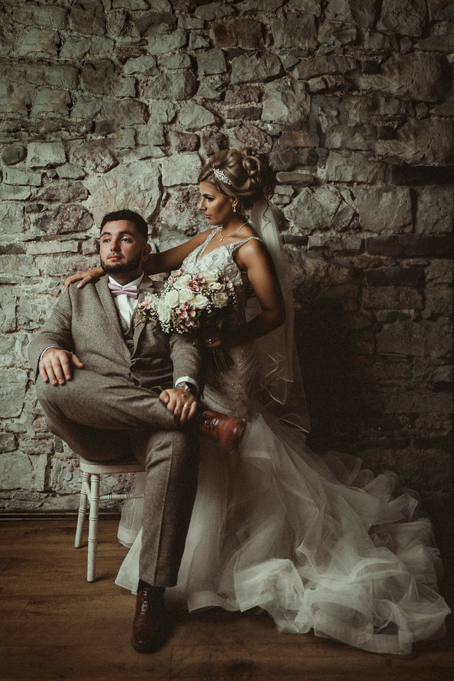 gorgeous couple by a historic stone wall