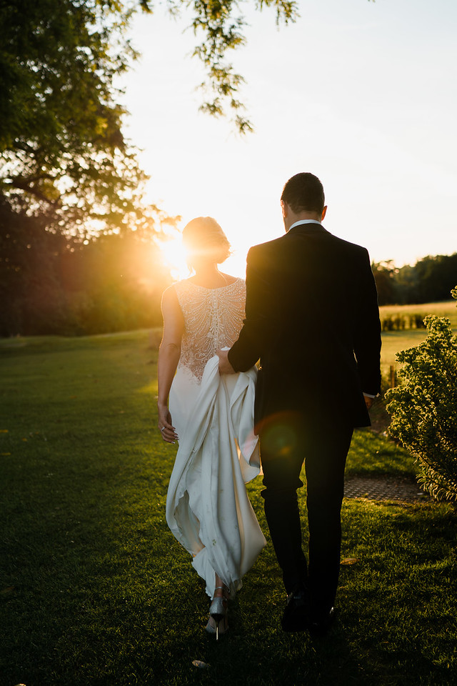 couple walk through the grounds as the sun is setting