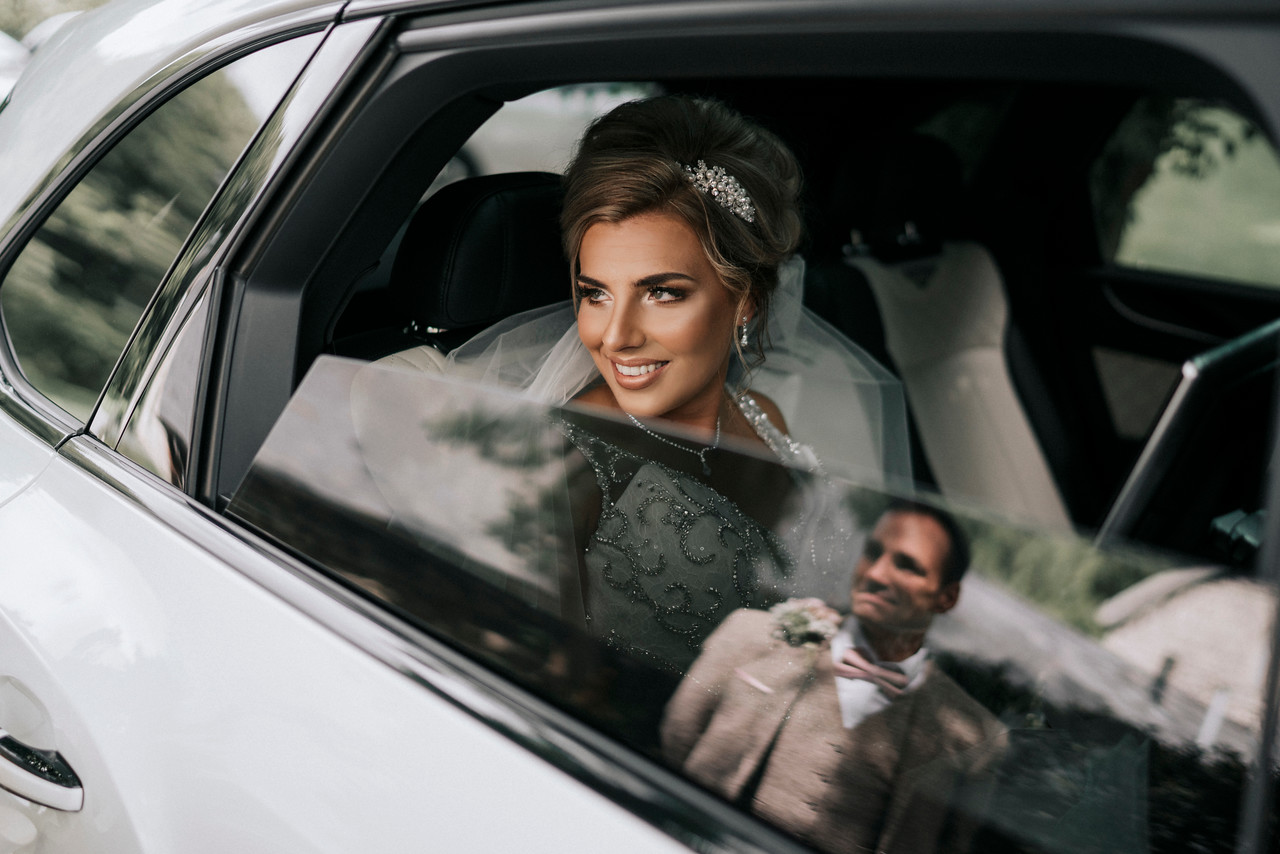 bride in a car and groom in reflection| Court Colman Manor