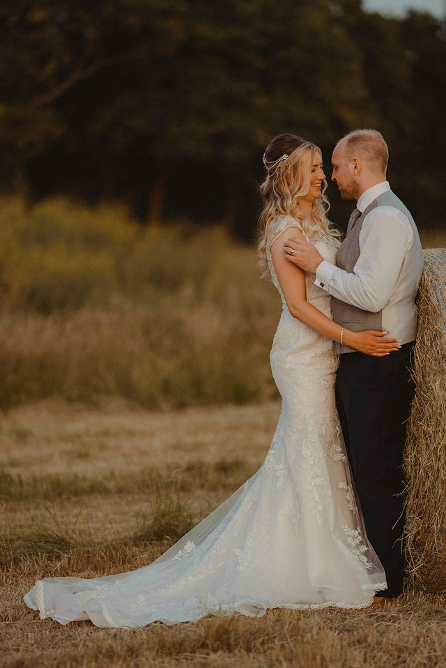 The bride and groom hold each other in their countryside setting