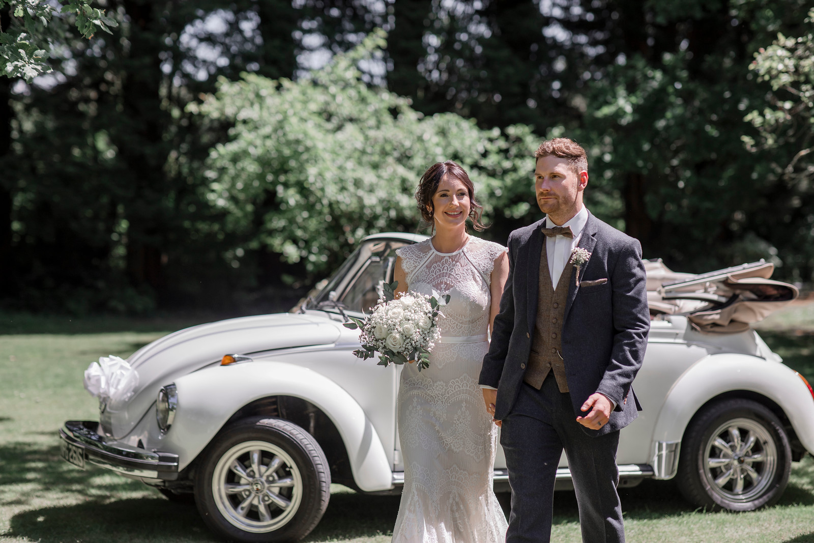 The classic Volkswagen car in the background as bride and groom walk just in front of the wedding car