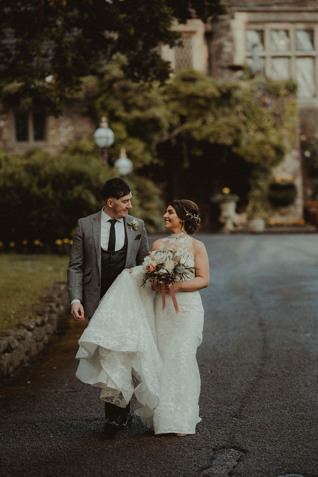 bride and groom walks down the road smiling at each other