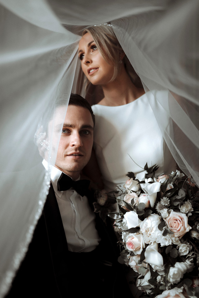 bride and groom are captured under the brides veil