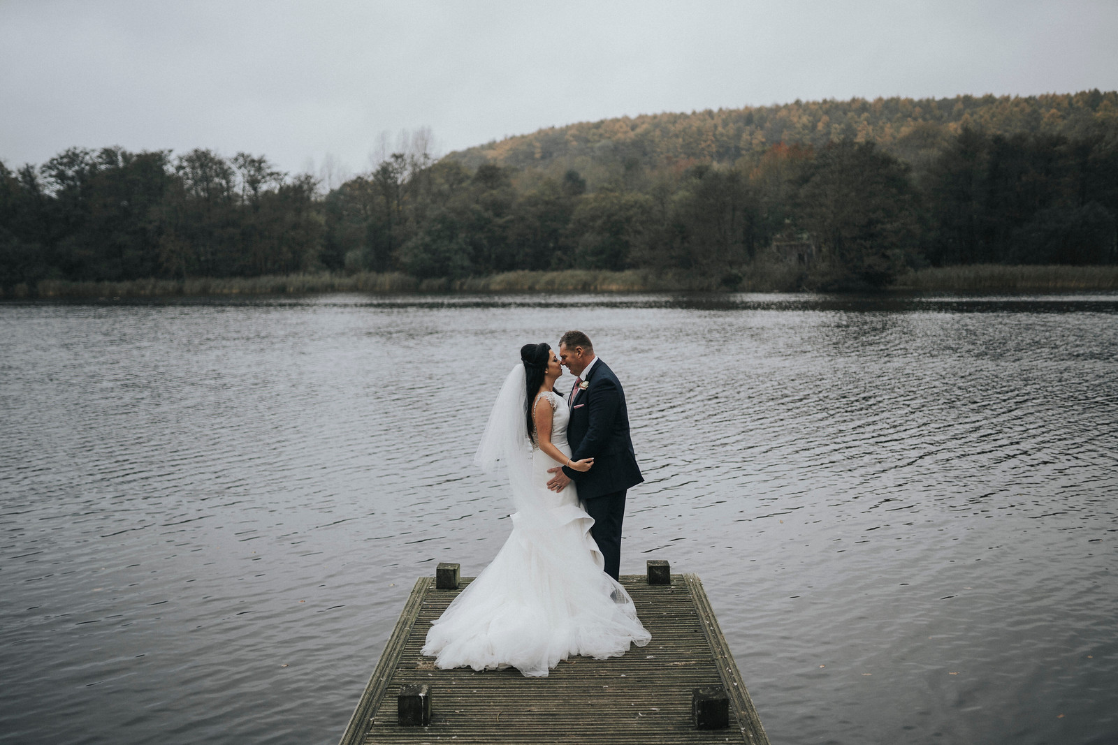 bride and groom kissing by the glistening lake