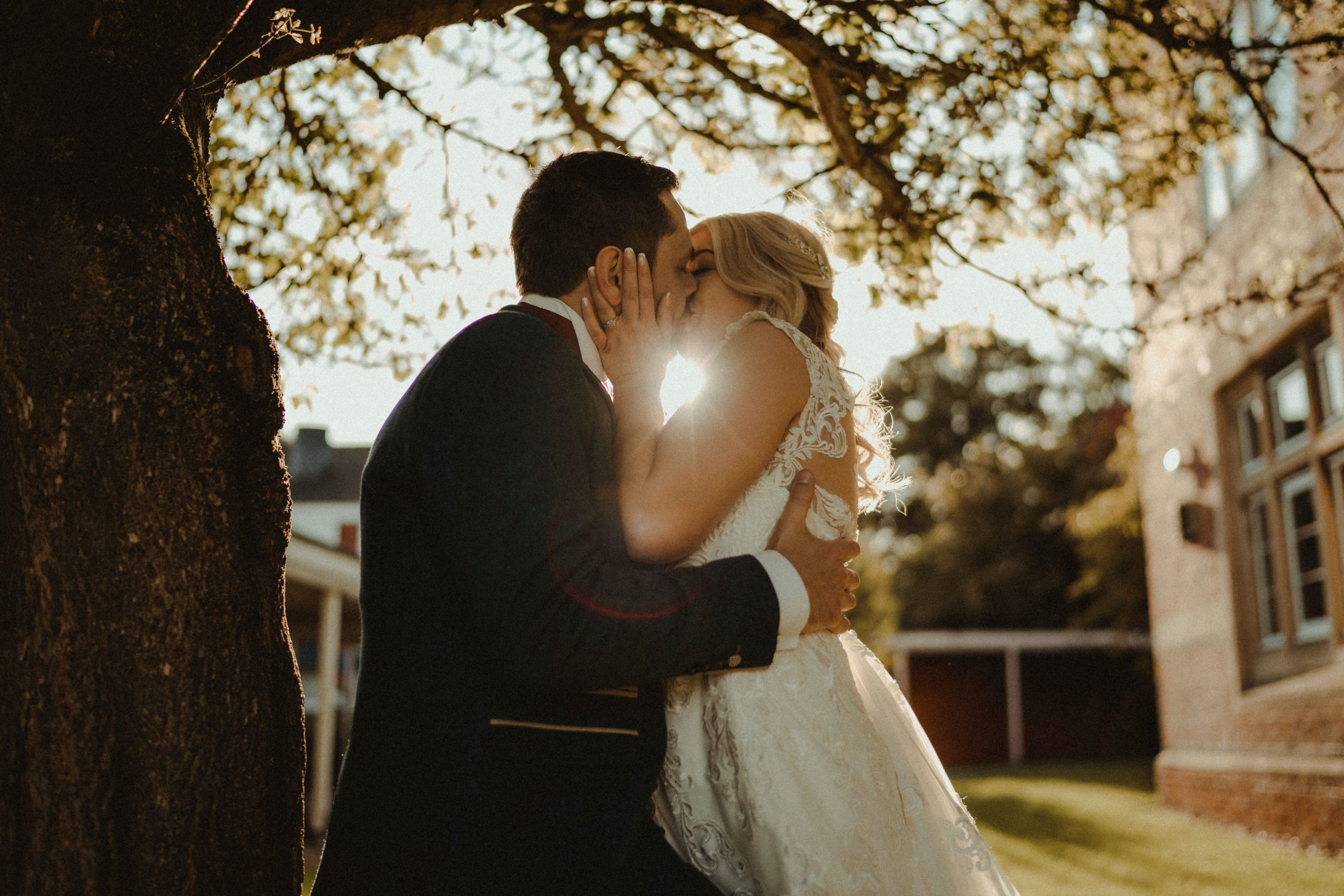 Bride and groom kiss in the sunset, autumn wedding