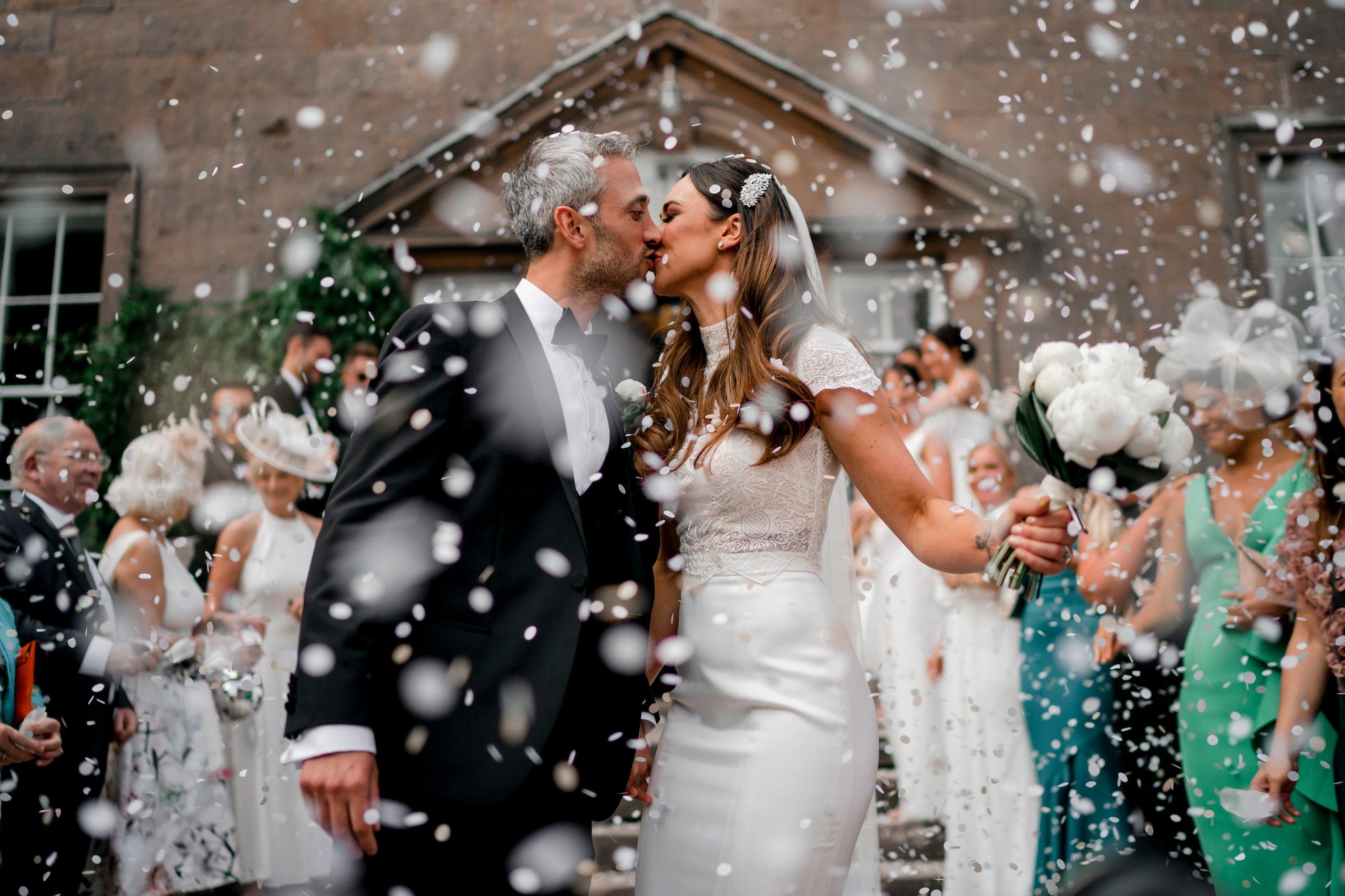Bride and groom kiss whilst family and friends throw confetti over them |First love