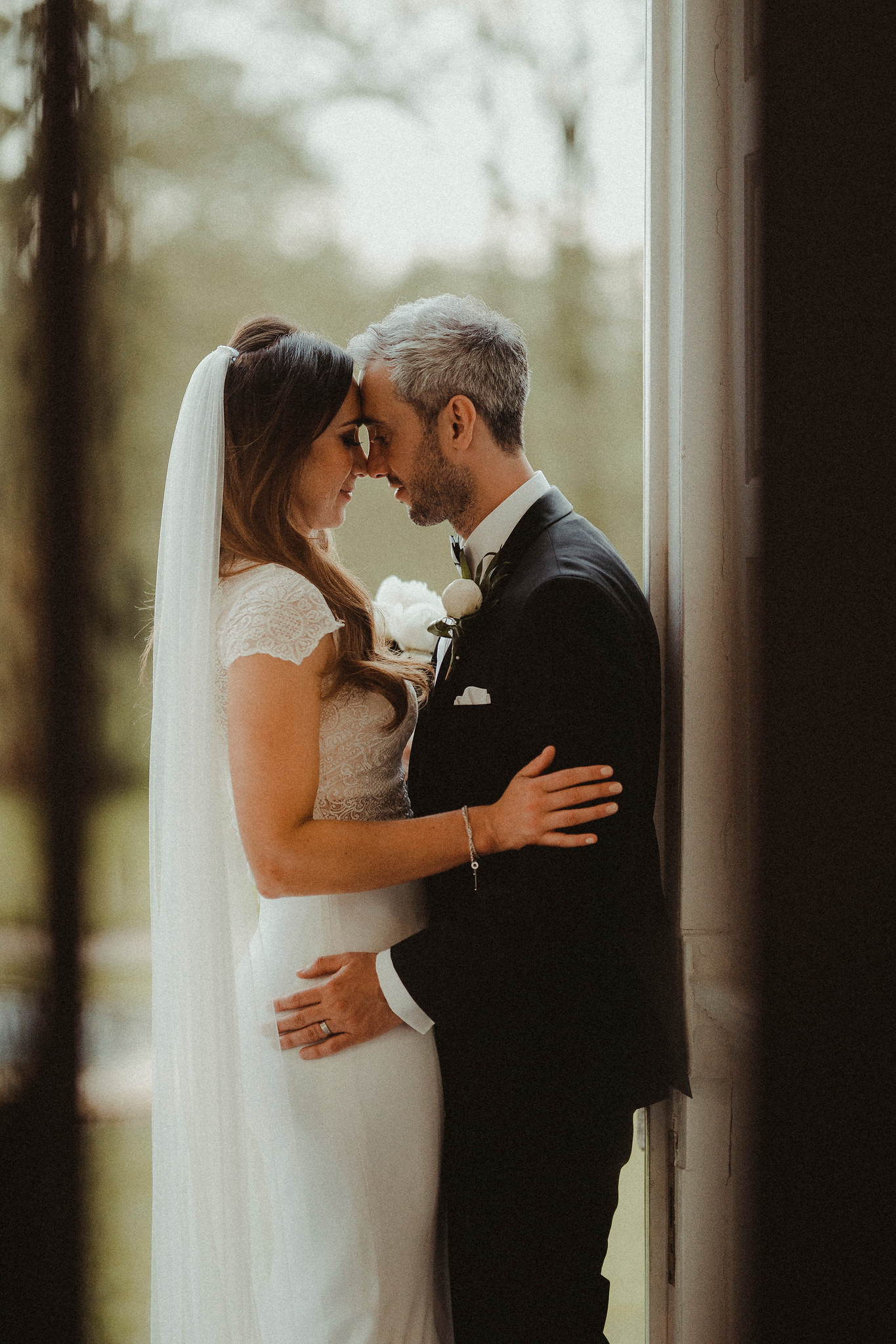 The couple look at each other as they stand in the doorway of their venue. Wedding Pictures