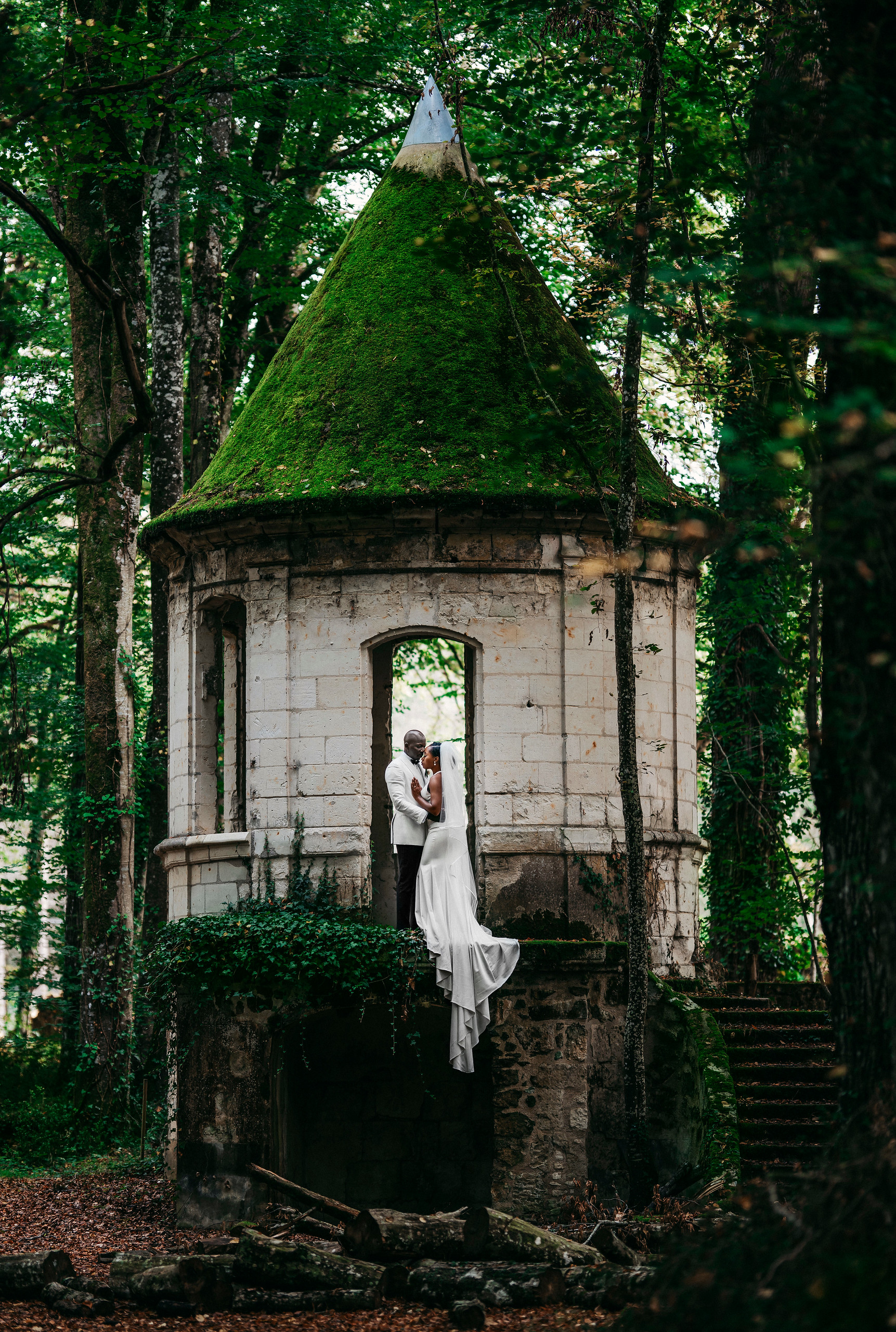 Bride and groom standing in the archway of a historic tower