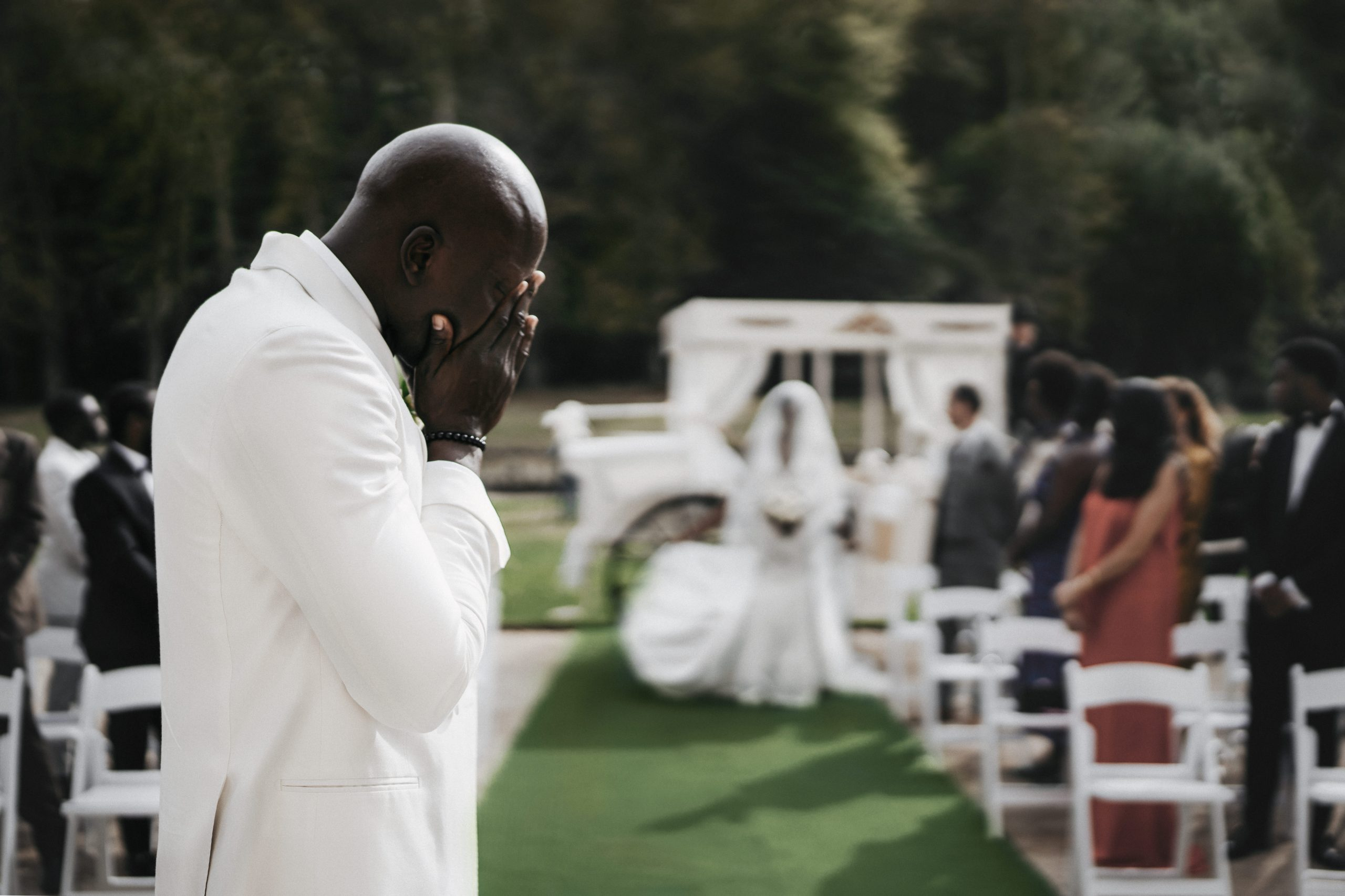 Groom covers his face with his hands as he gets emotional from seeing his bride for the first time | Elegant wedding