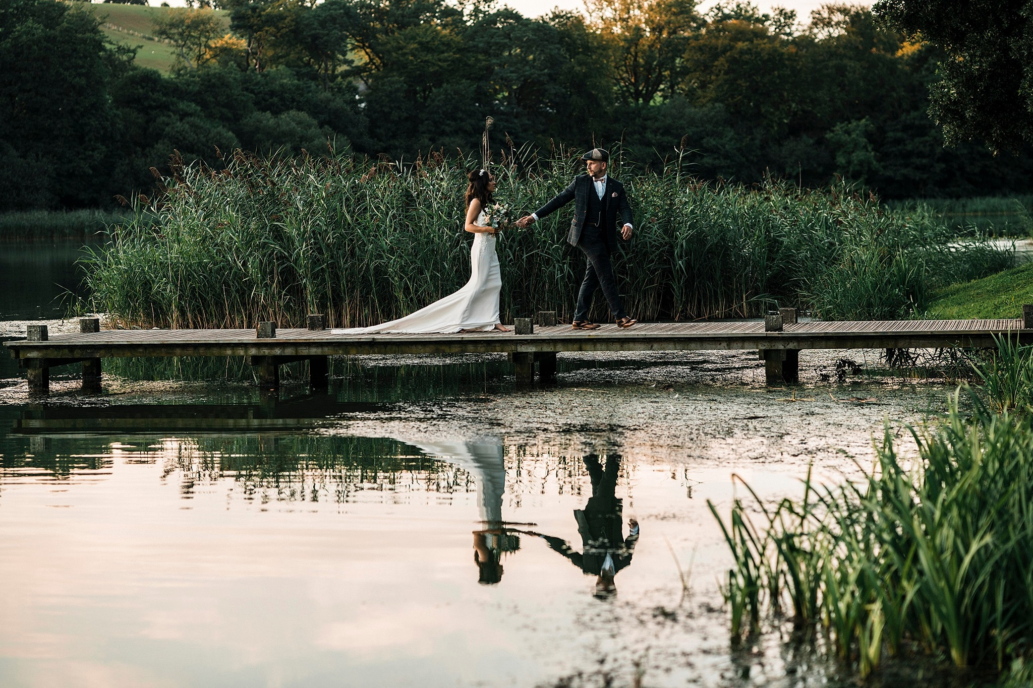 Bride and groom walking by the glistening lake
