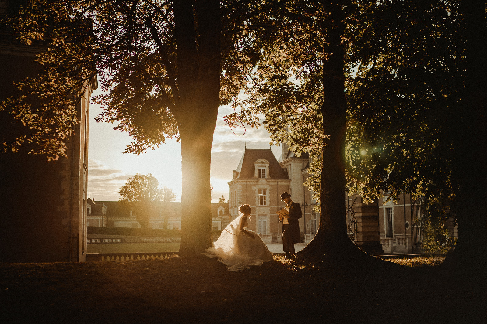 Bride and groom between the middle of trees, as the sun is setting in the background