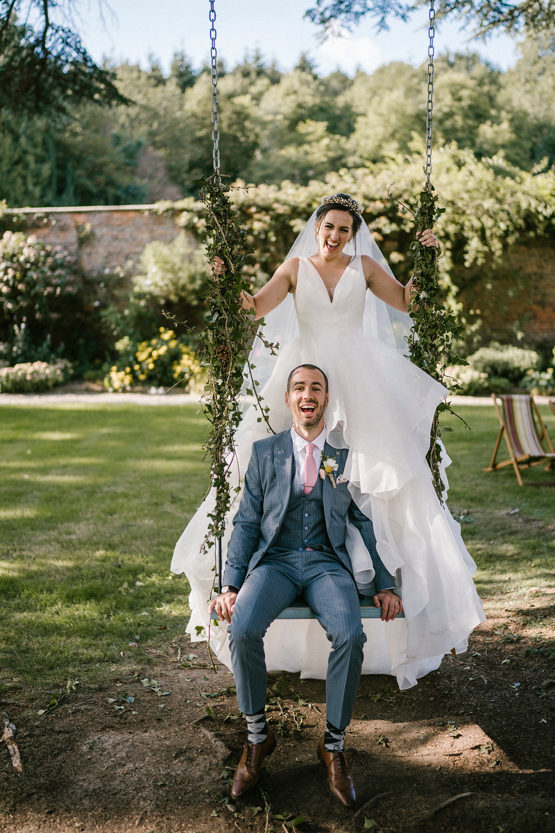 Bride and groom having a laugh on the wedding swing  Wedding photo