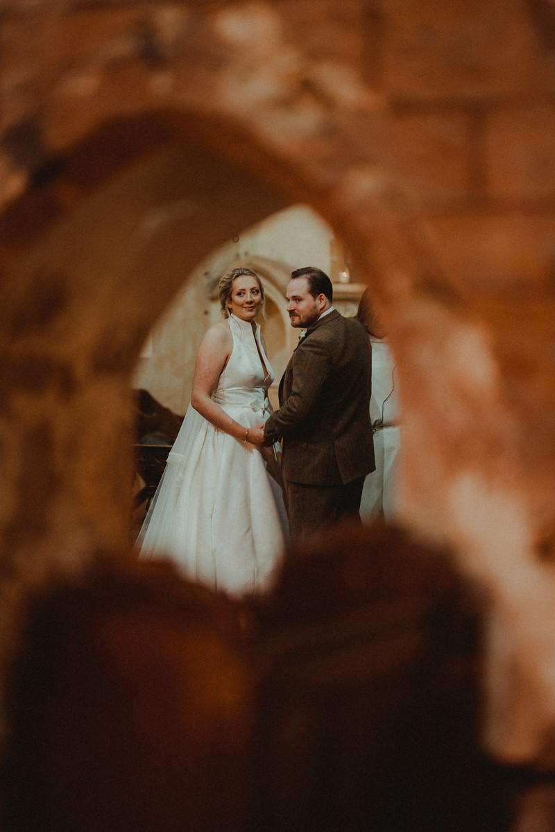 Bride and groom smile as they become husband and wife, the picture is taken though a hole  Unique and creative picture