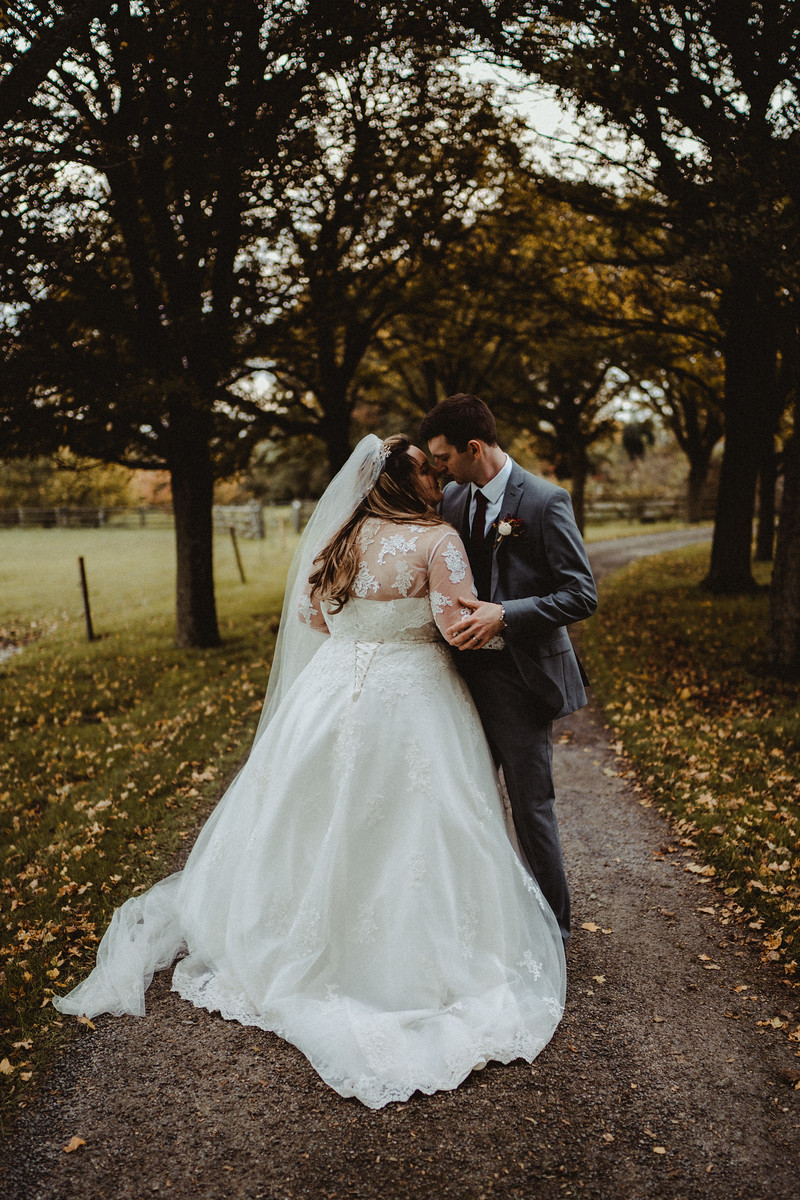 Bride and groom hold each other in the middle of the beautiful scenery of their venue| Cotswold Wedding Venue