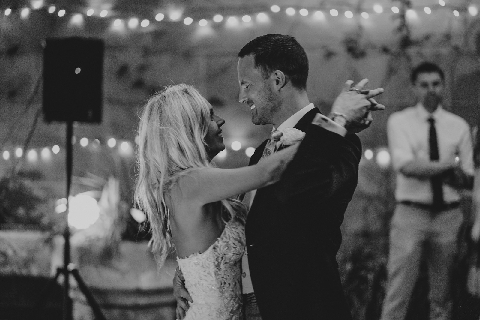 Bride and grooms fire dance, they smile at each other. Black and white image