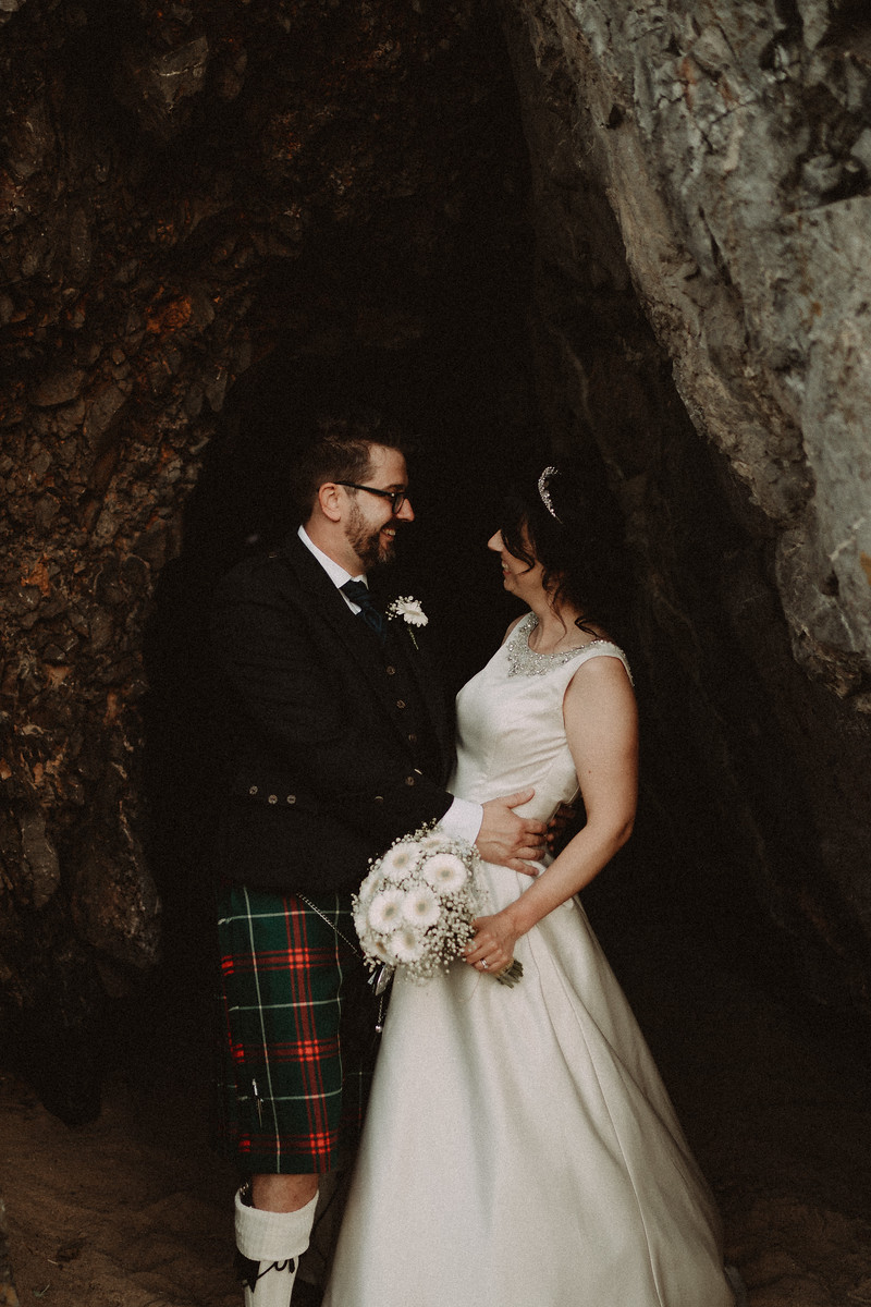 Bride and groom look at each other as they stand in a cave| Fun Wedding