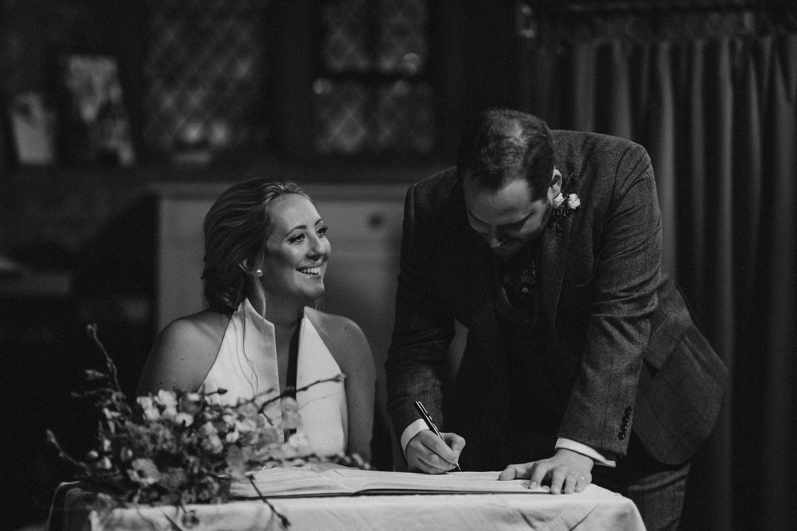 Bride and groom signing the book as the bride looks up and smiles| Unique wedding venue