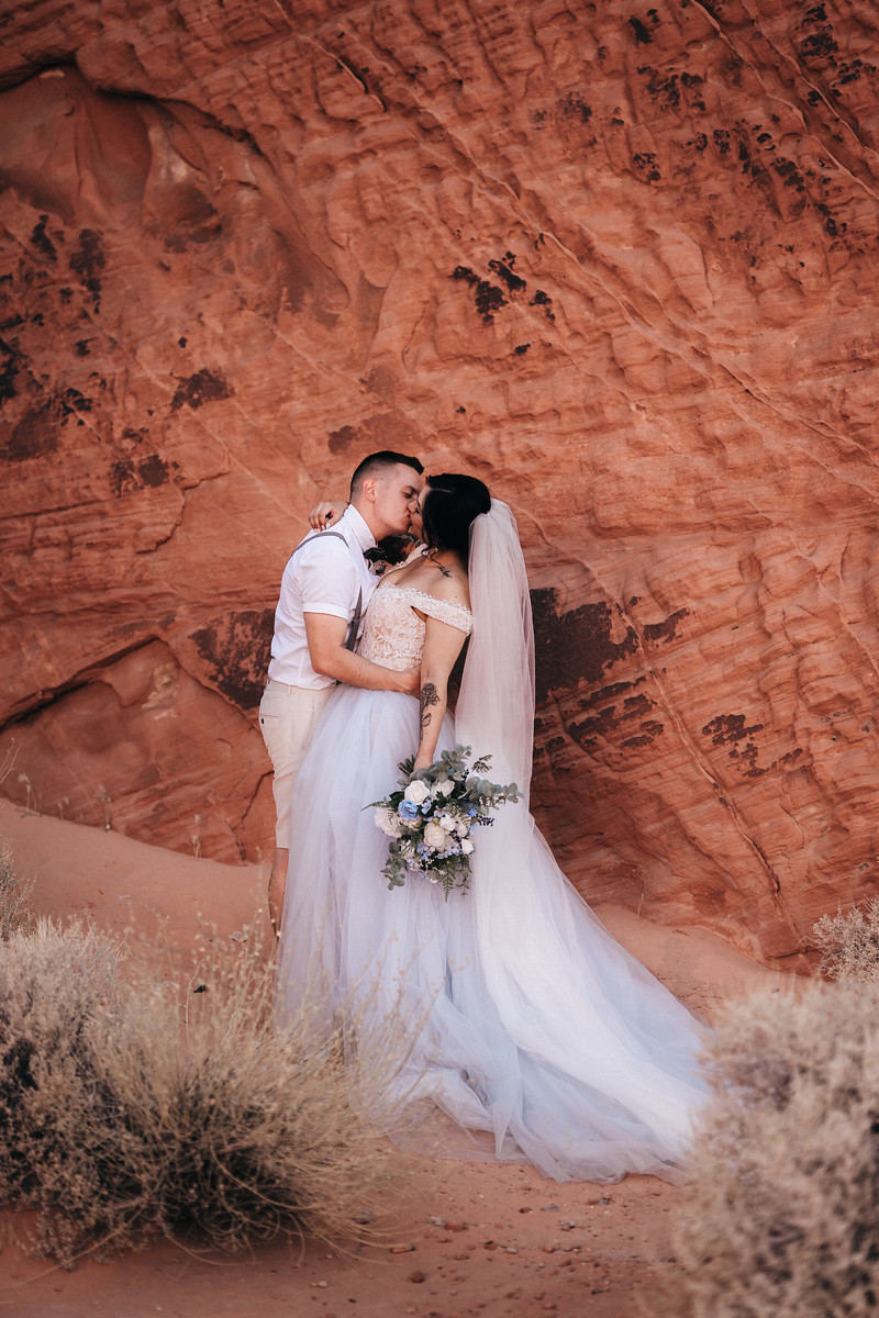 The bride and groom kiss surrounded by the rock formations of their venue