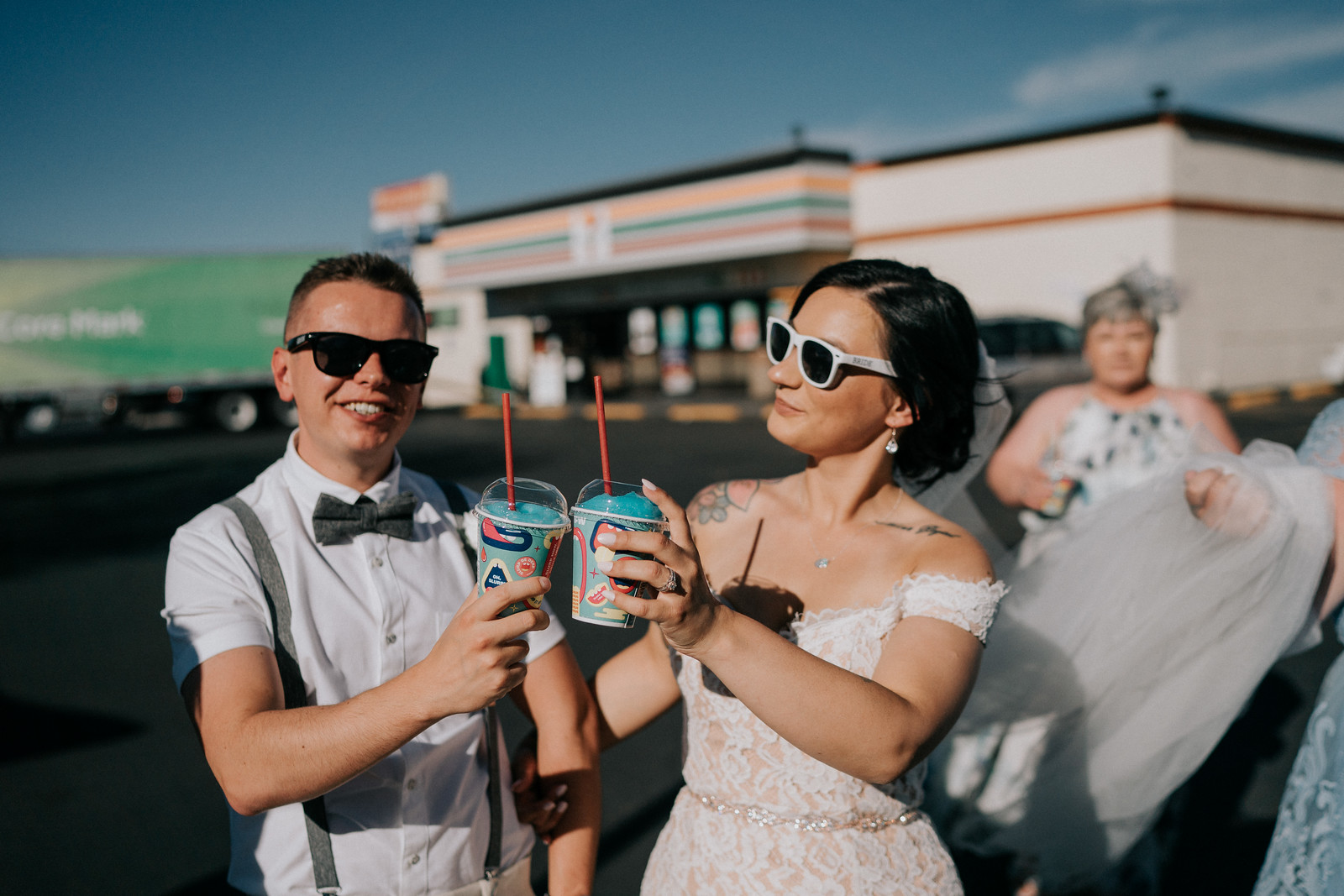 The couple smile and show their slushes from 7 Eleven, celebrating their wedding with family and friends