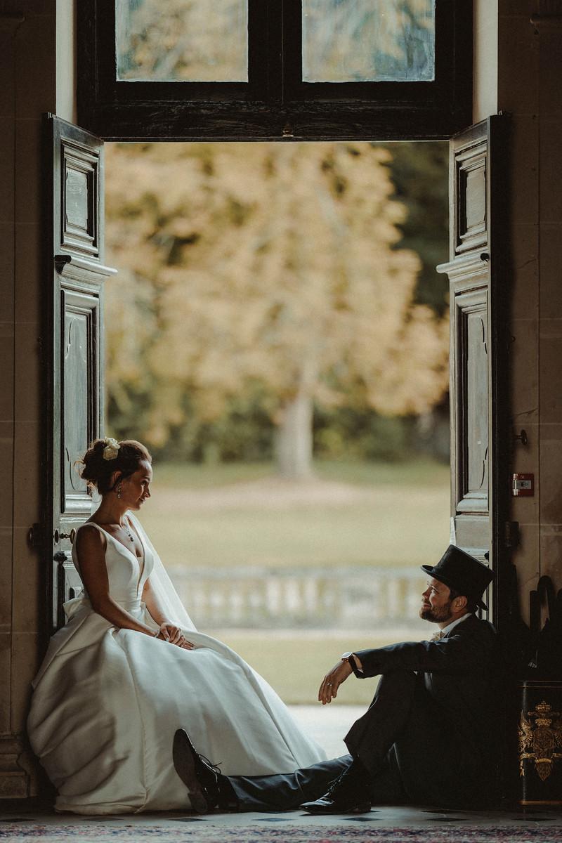 Bride and groom sat in the doorway of their venue, looking at each other