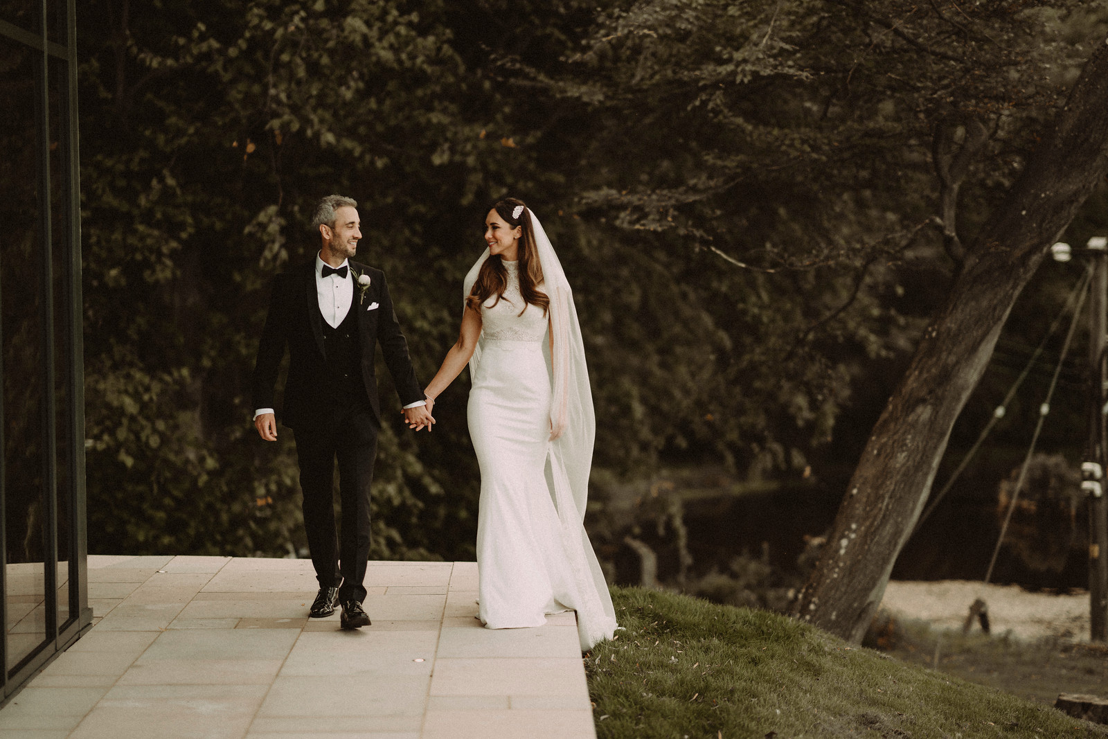 Bride and groom walk outside their venue holding hands and smiling at each other. Wedding pictures