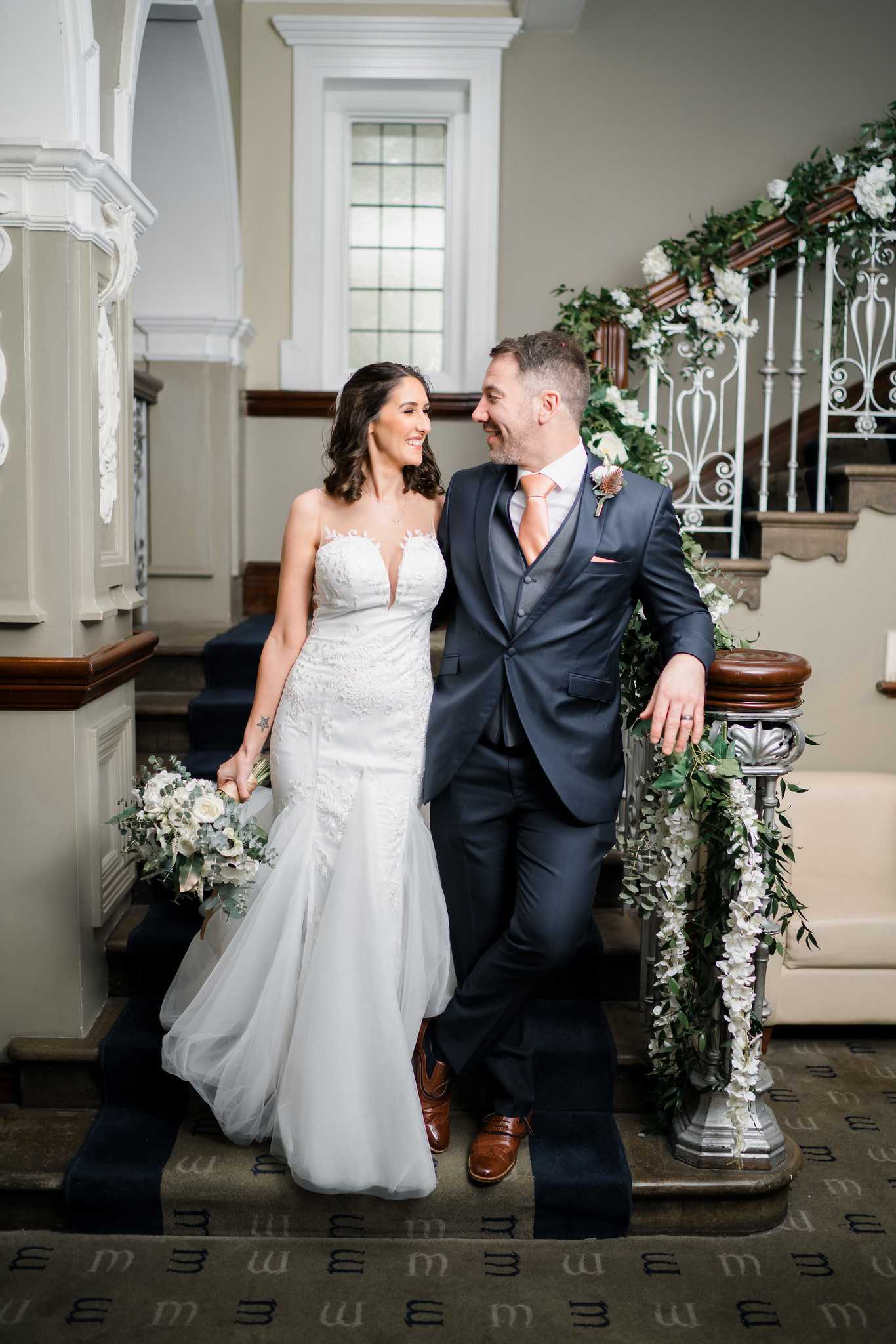 Bride and groom look at each other and smile as they stand at the bottom of the stairs in the venue