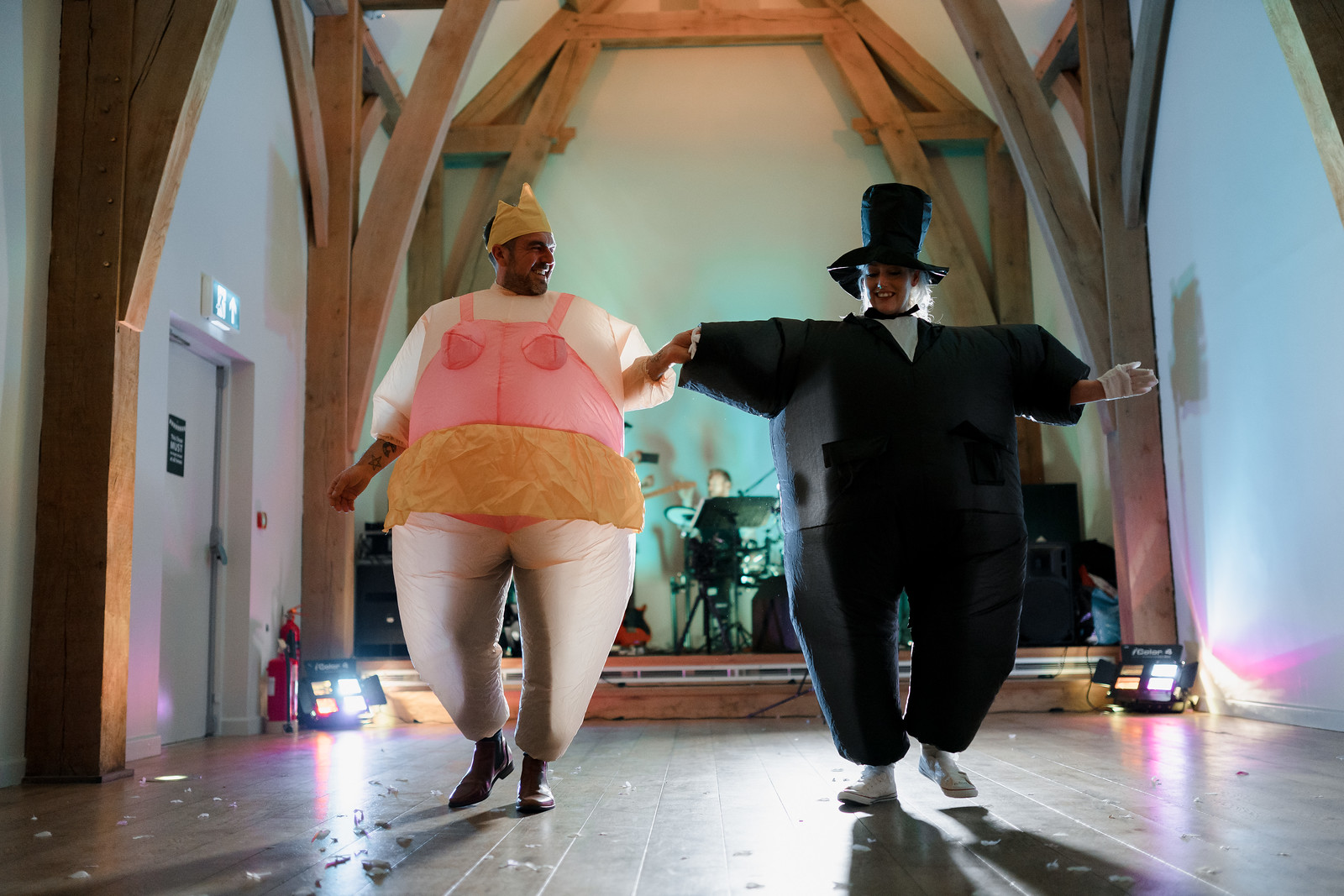 Bride and groom dance in inflatable costumes for their first dance - The Mill Barns