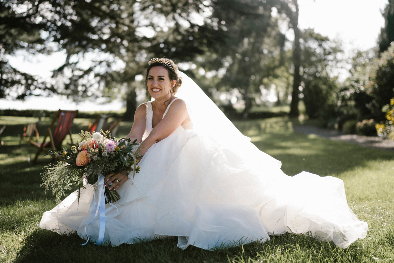Bride smiles as she is sat in the middle of the beauty of her venue  Wedding photo