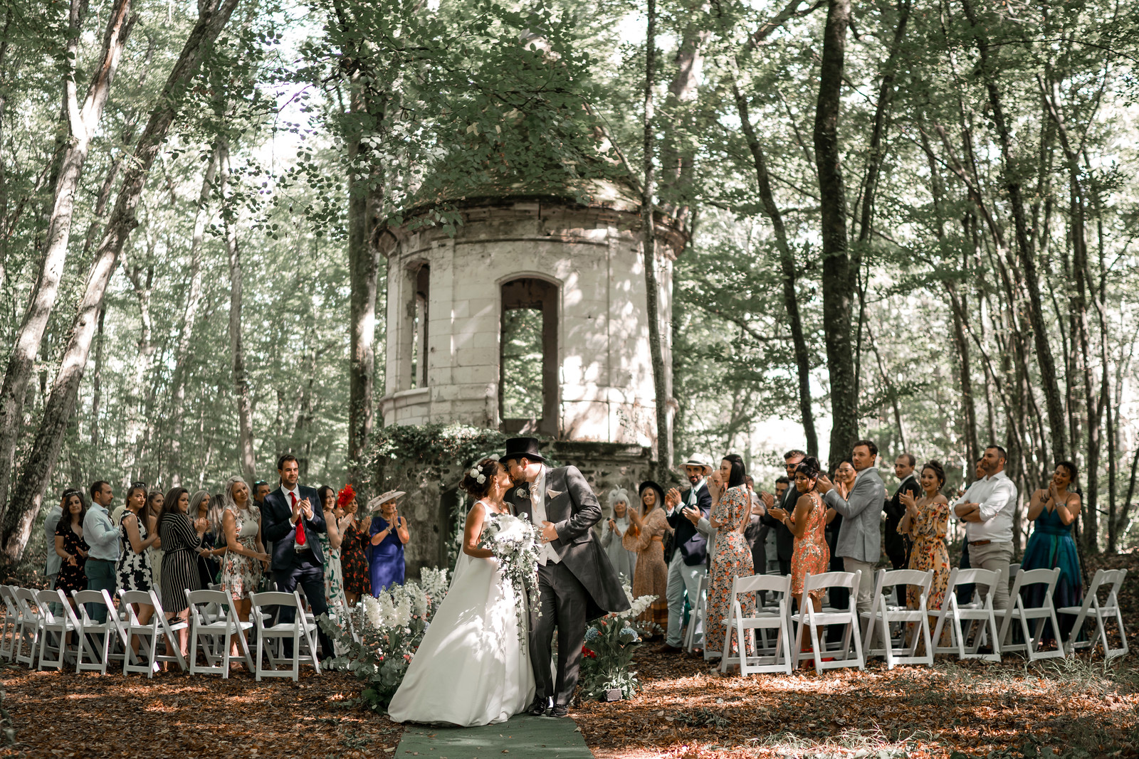 Bride and groom kiss as their family and friends are clapping