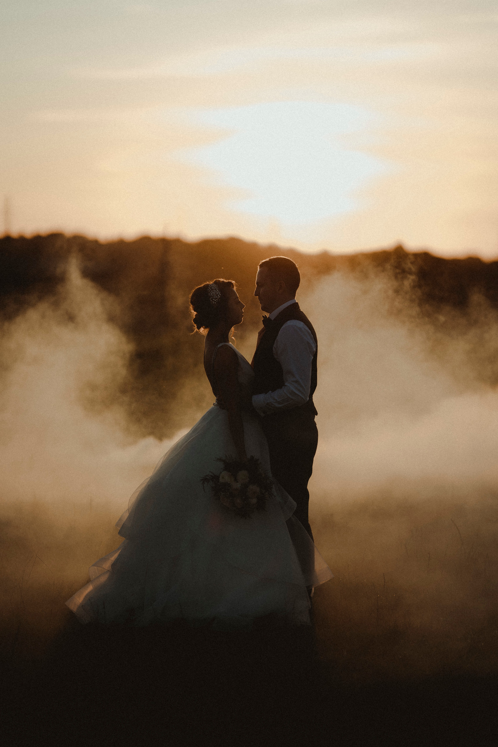 Bride and groom look at each other as the sun is setting and smoke is surrounding them