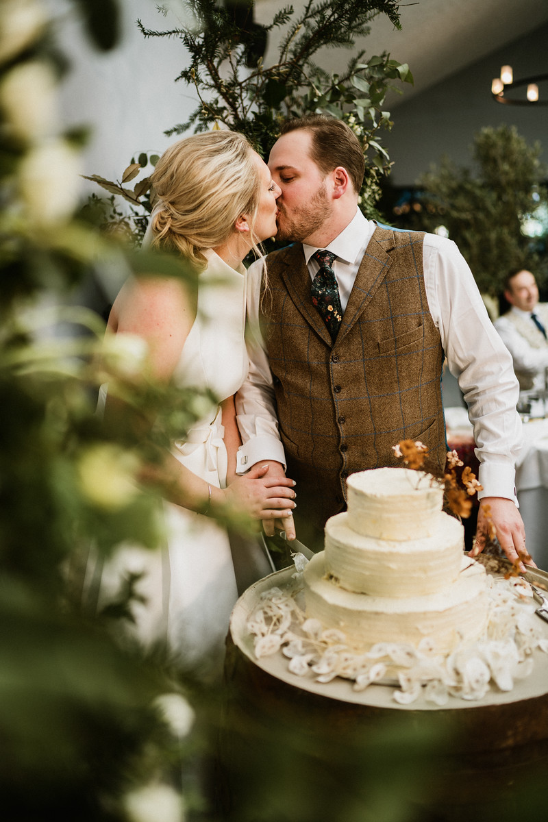 Bride and groom kiss as they cut their wedding cake| Rustic wedding venue