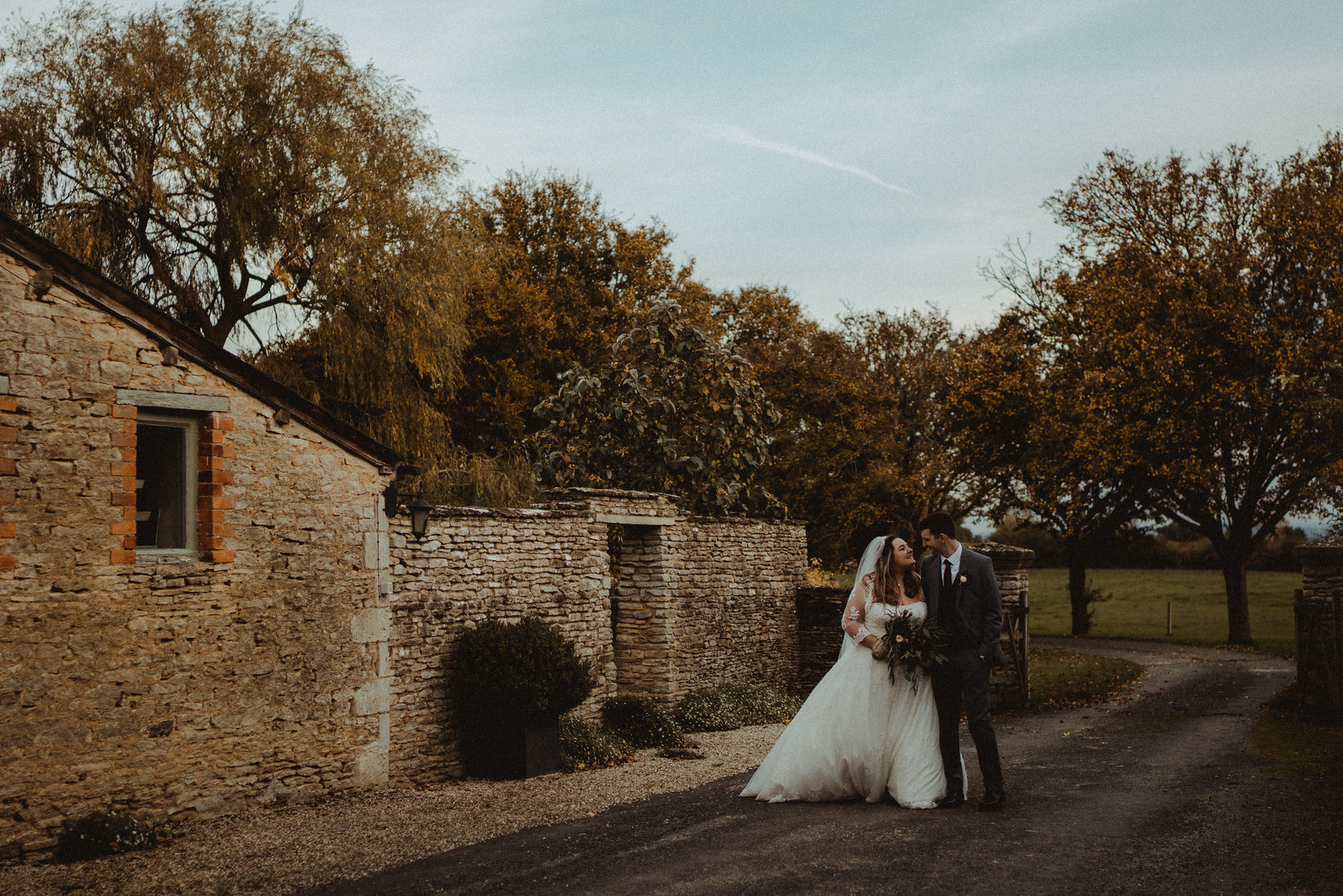 Bride and groom smile as they walk through the outdoors of their venue| Cotswold Wedding Venue