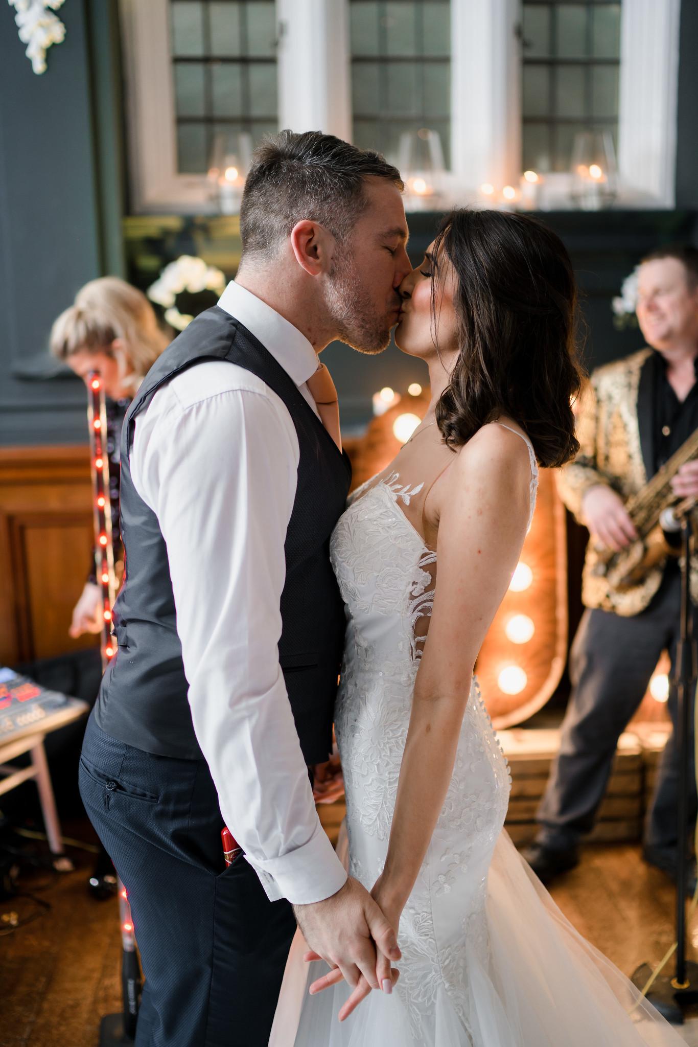 Bride and groom kiss on the dance floor