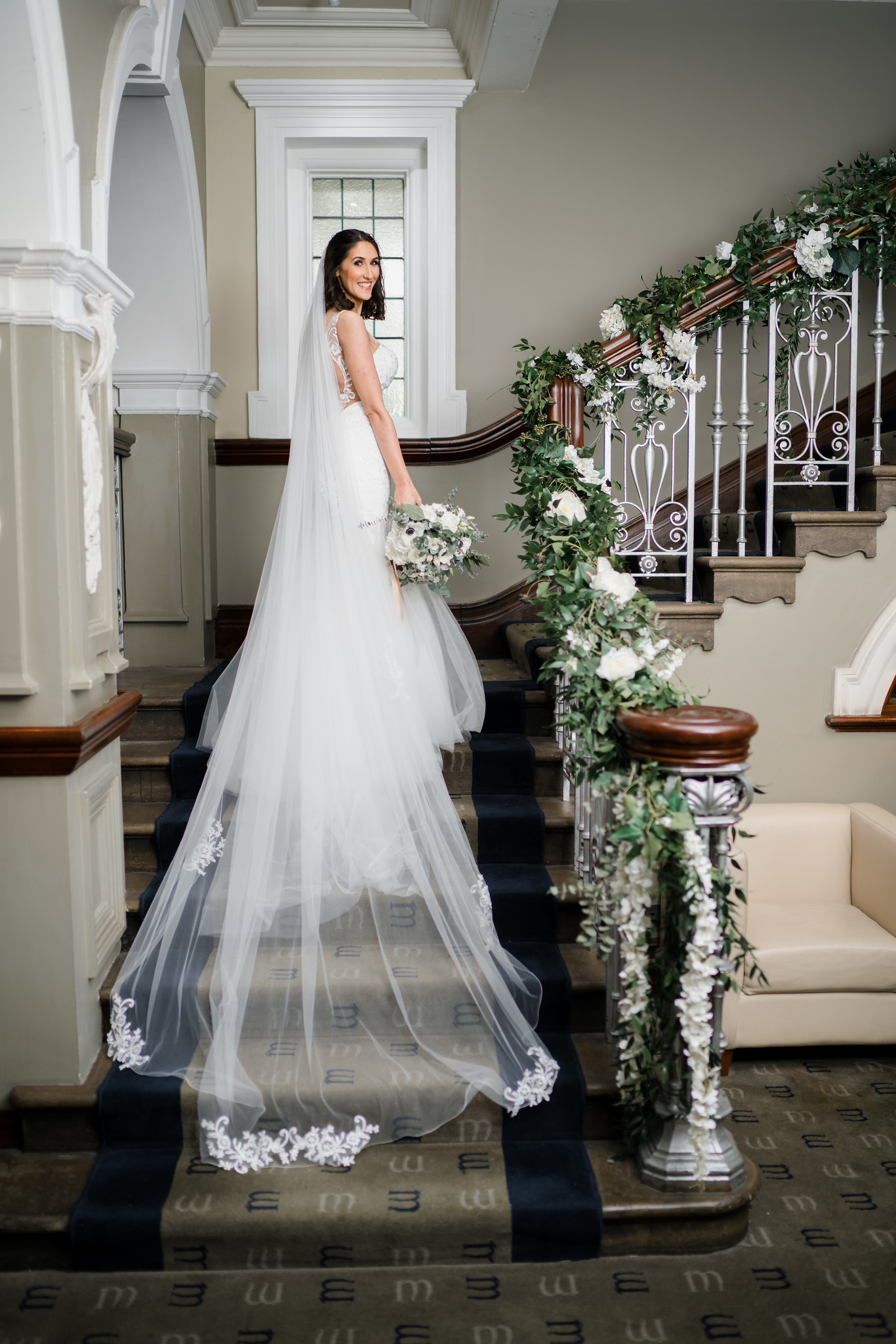 Bride looks back as she stands on the steps in the venue, her vail covers the steps behind her