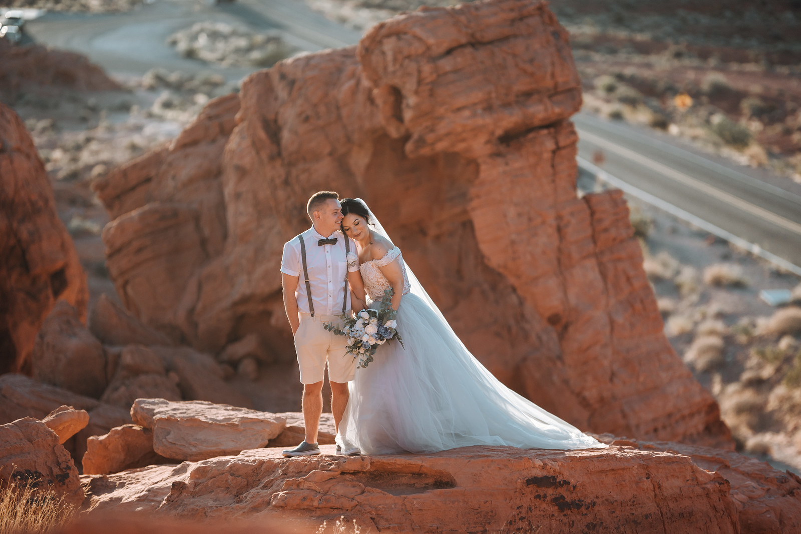 Bride and groom stand on rocks as they show their love