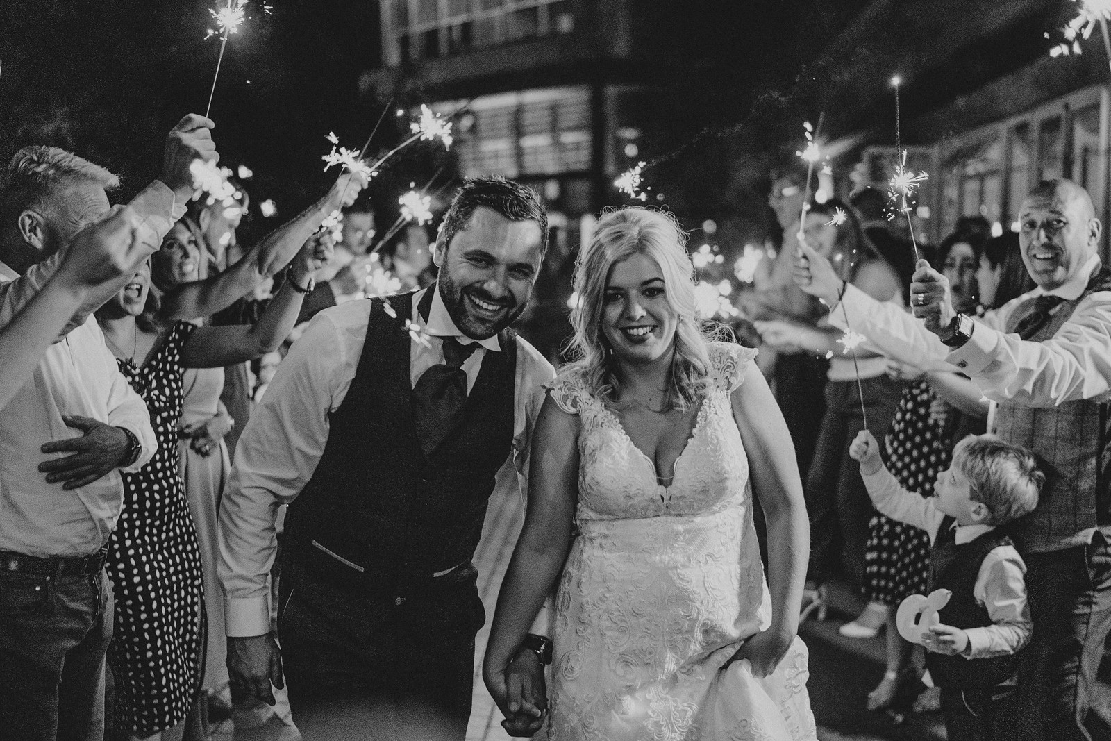 Bride and groom smile as their family and friends hold sparklers around them  Autumn wedding