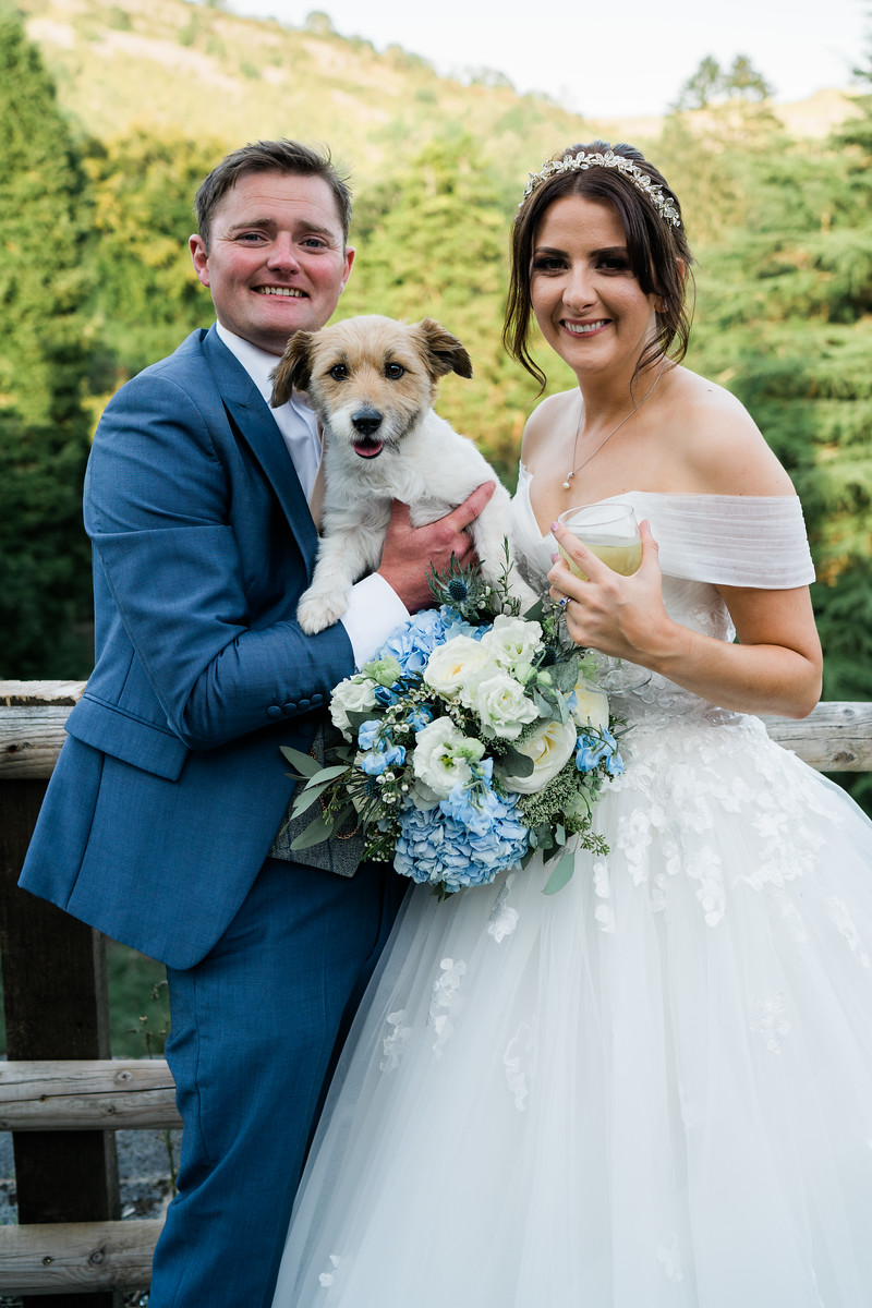 a family photo of the bride, groom, and their dog