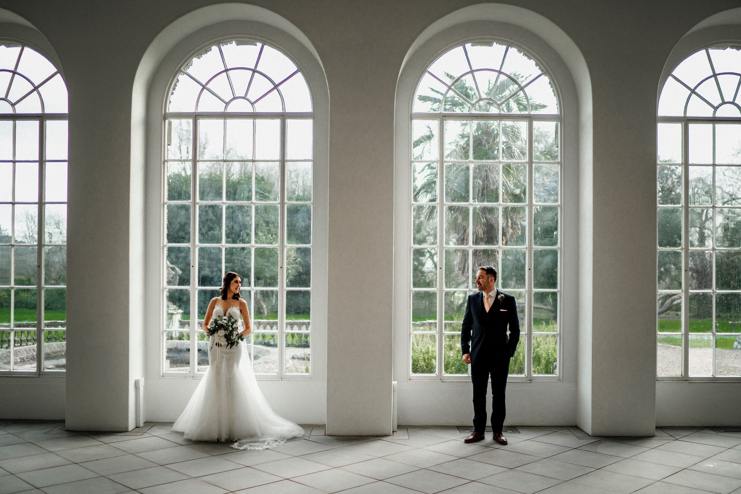 Bride and groom stand in front of the grand windows