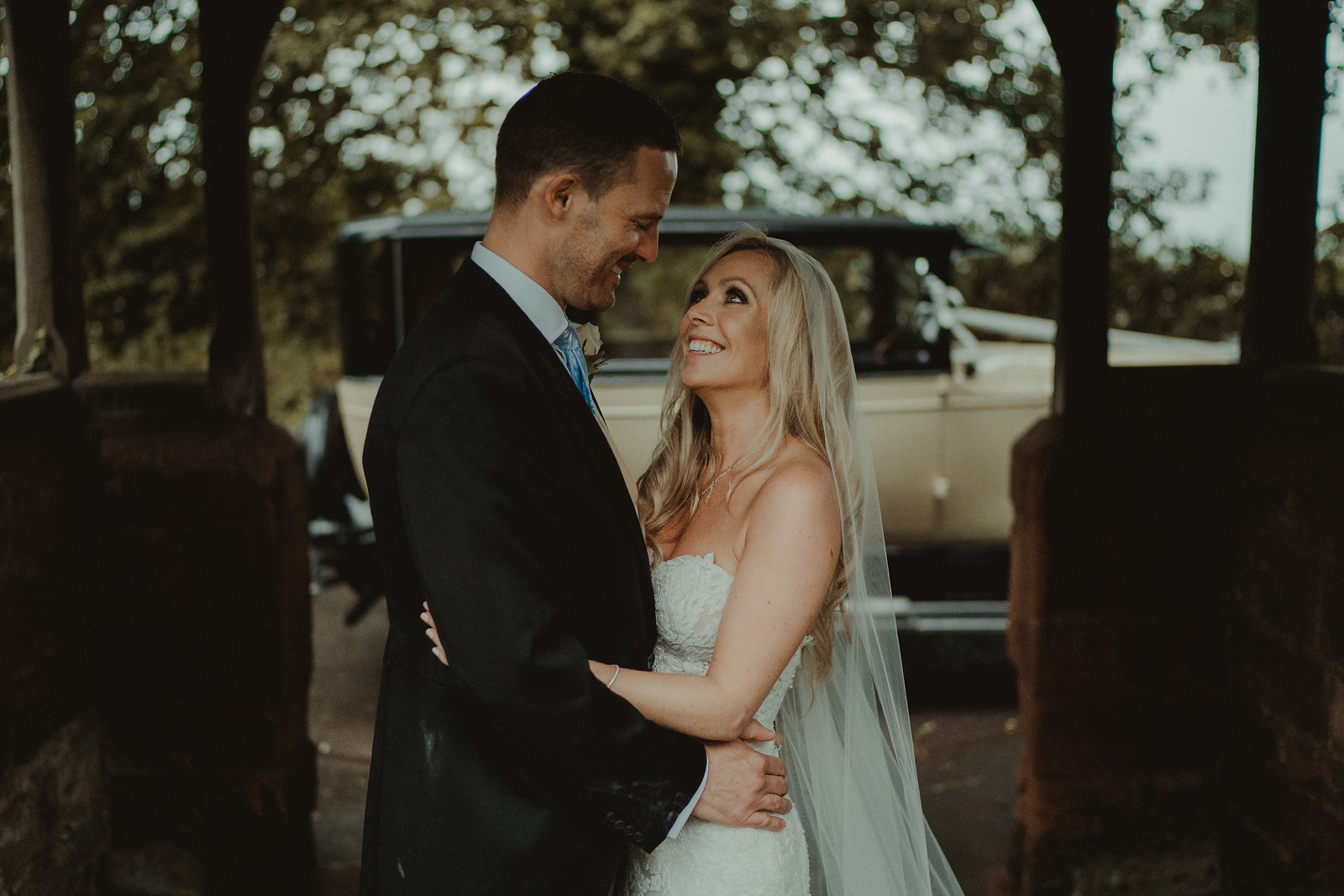Bride and groom look at each other and smile underneath an archway