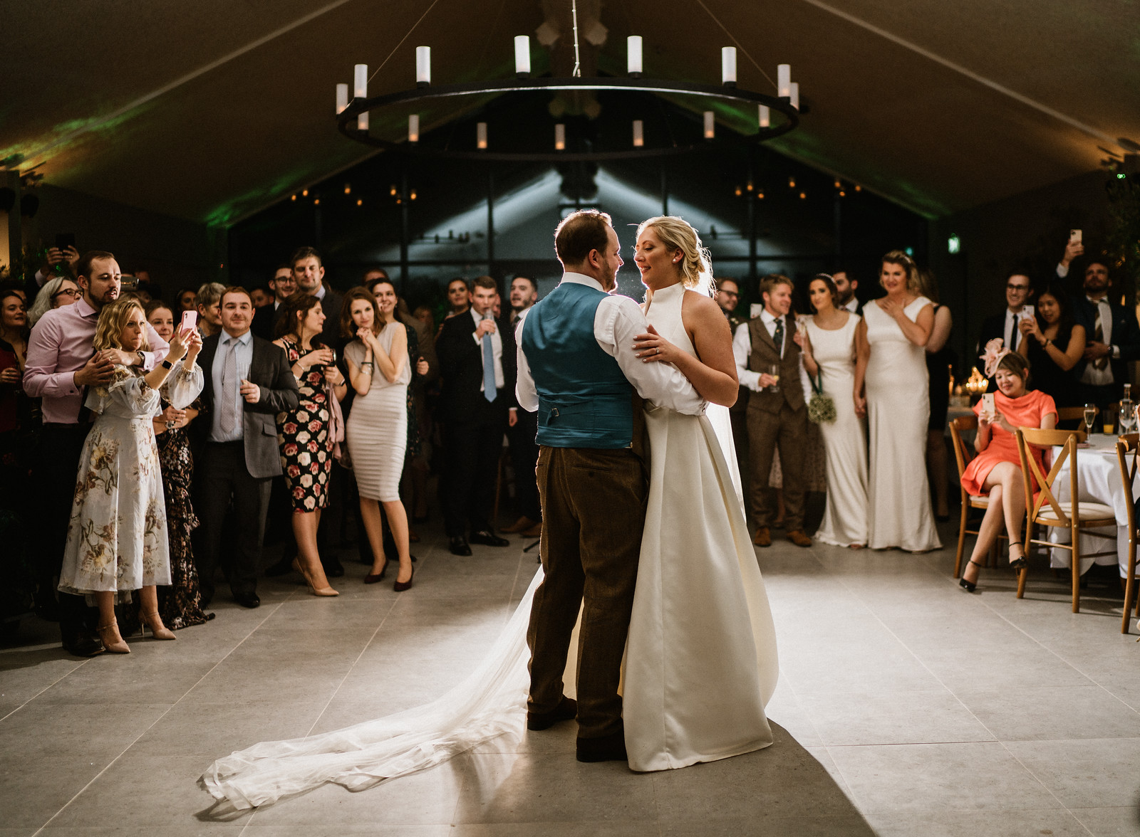 Bride and groom dance as family and friends watch| Unique wedding venue
